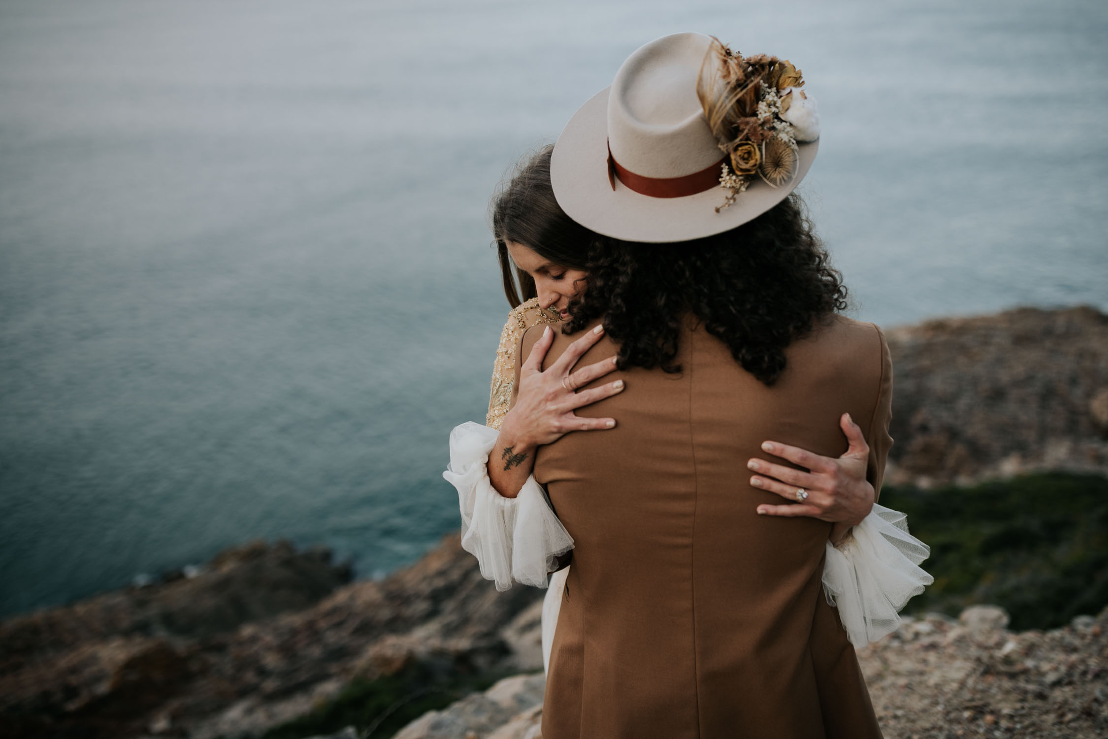 Bride affectionately holds onto her groom as they stand on a cliff overlooking the beach and sea at boho wedding shoot