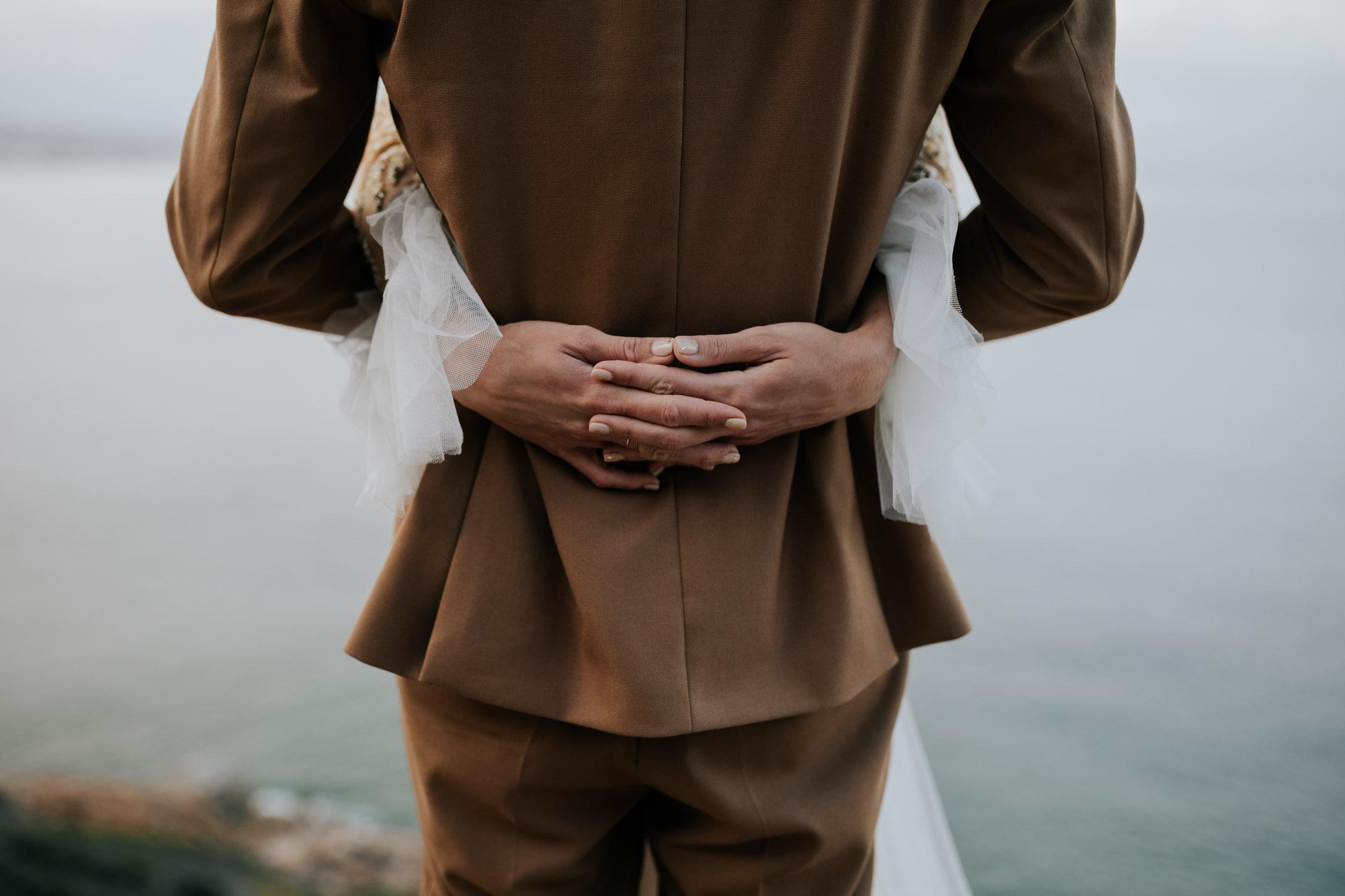 Groom holds bride overlooking ocean