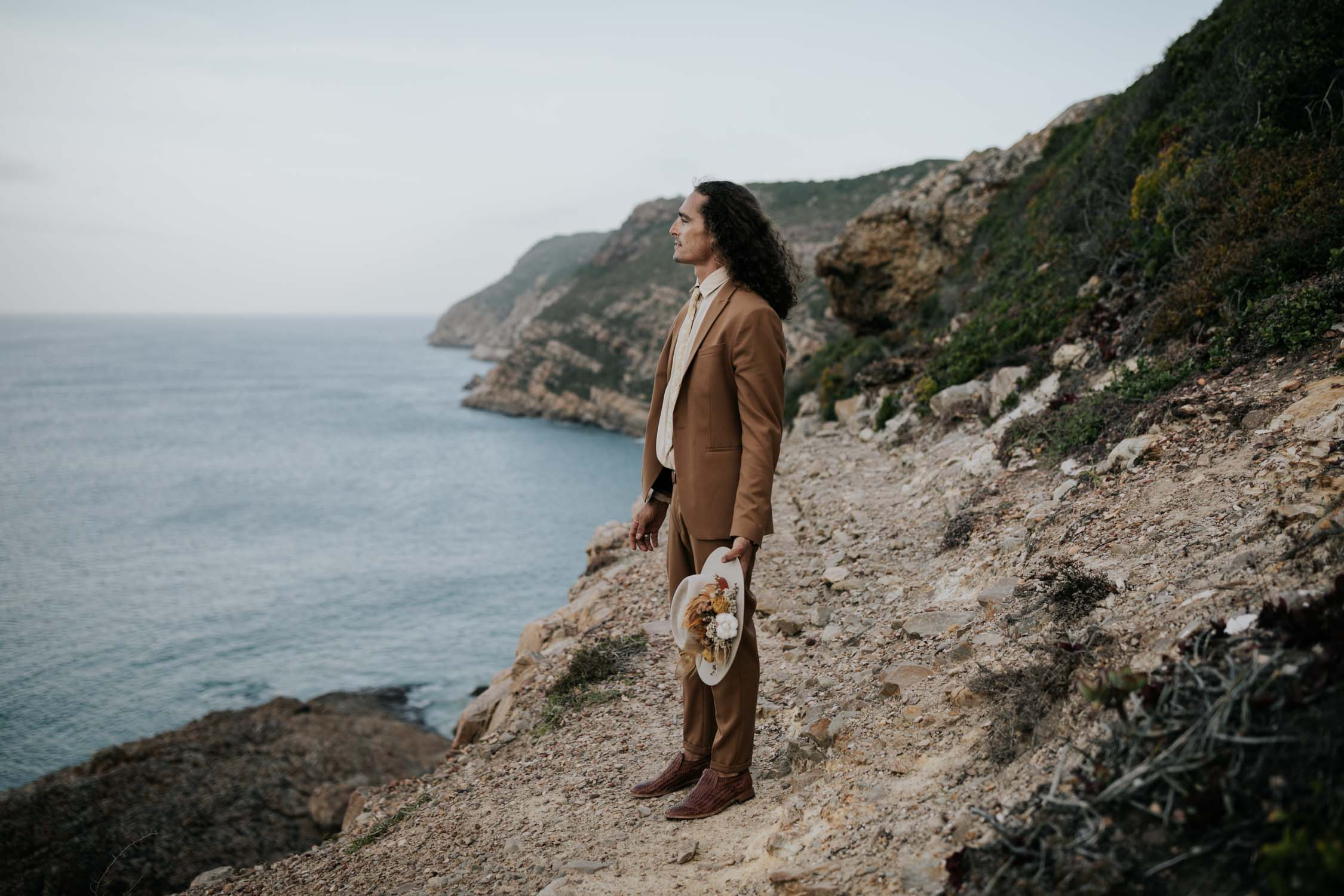Bohemian groom with long curly hair wears brown suite, beige shirt and felt hat looks at the ocean