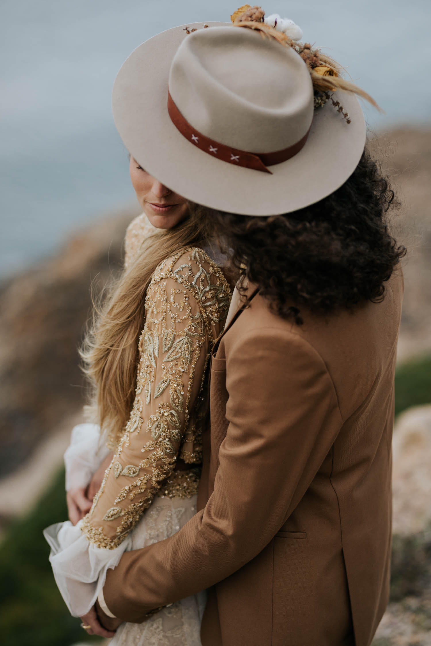 Photo by Vancouver Photographer of groom wearing brown suite, beige shirt, and felt hat holds bride wearing gypsy wedding dress with flared long sleeves, sheer skirt and gold detailed top at the ocean