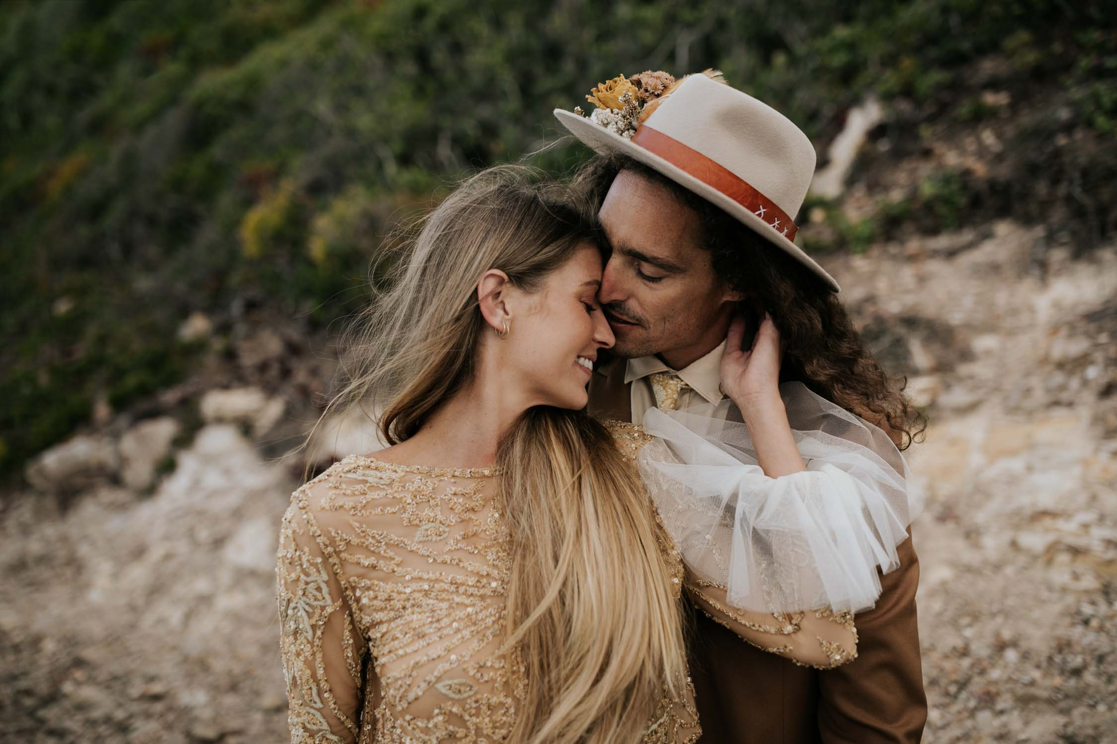 Photo by Vancouver Photographer of groom wearing brown suite, beige shirt, and felt hat kissing bride wearing gypsy wedding dress with flared long sleeves, sheer skirt and gold detailed top at the ocean