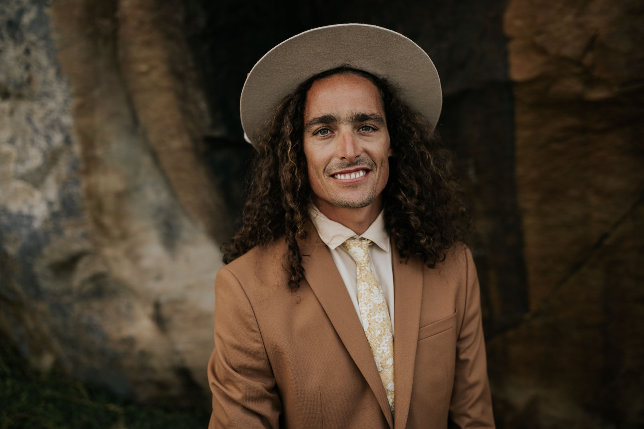 Bohemian wedding portrait of groom with long curly hair wears brown suite, beige shirt and felt hat