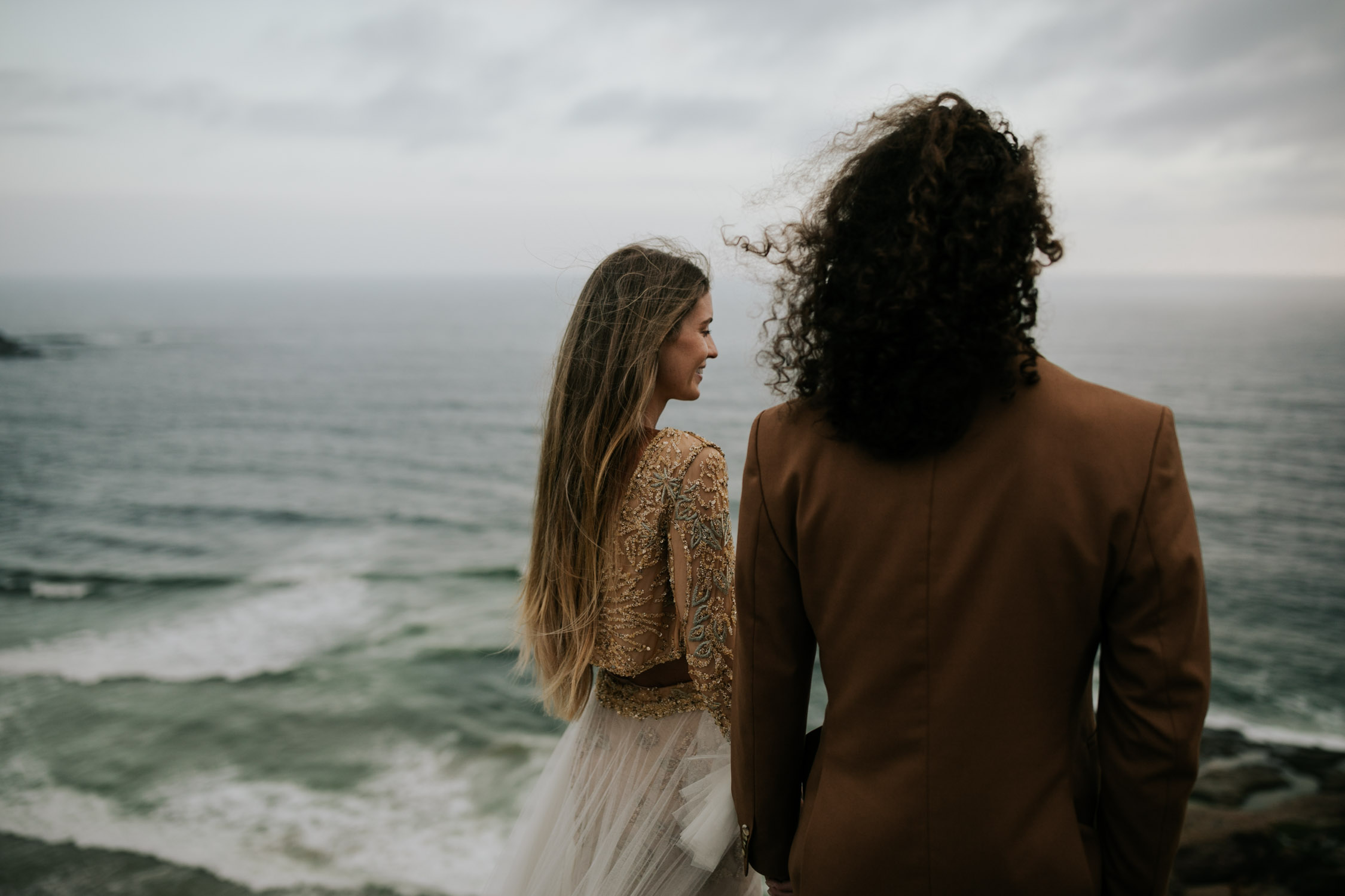 Beautiful boho gypsy bride stands with groom watching the ocean