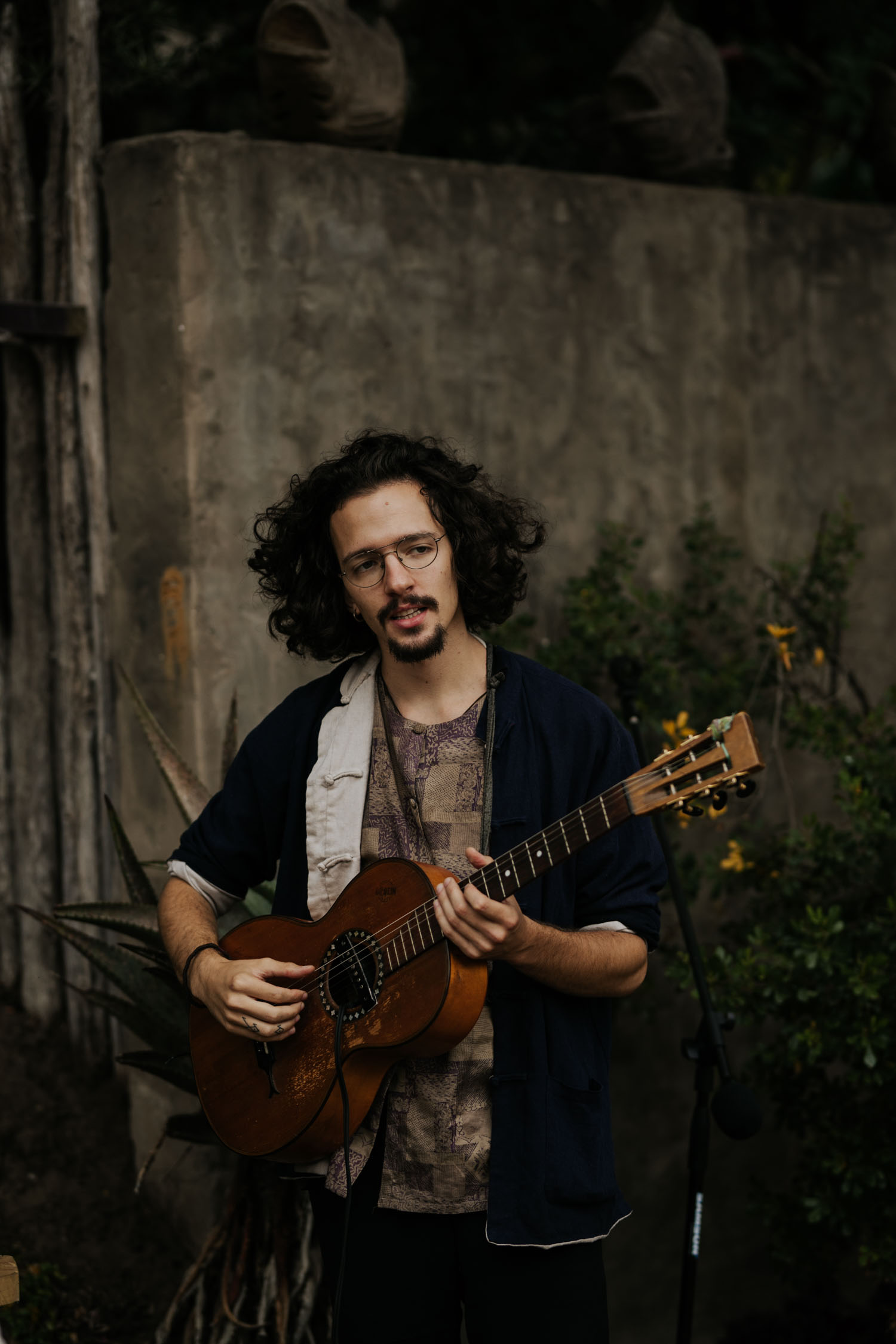 Indie curly haired wedding musician at boho wedding ceremony