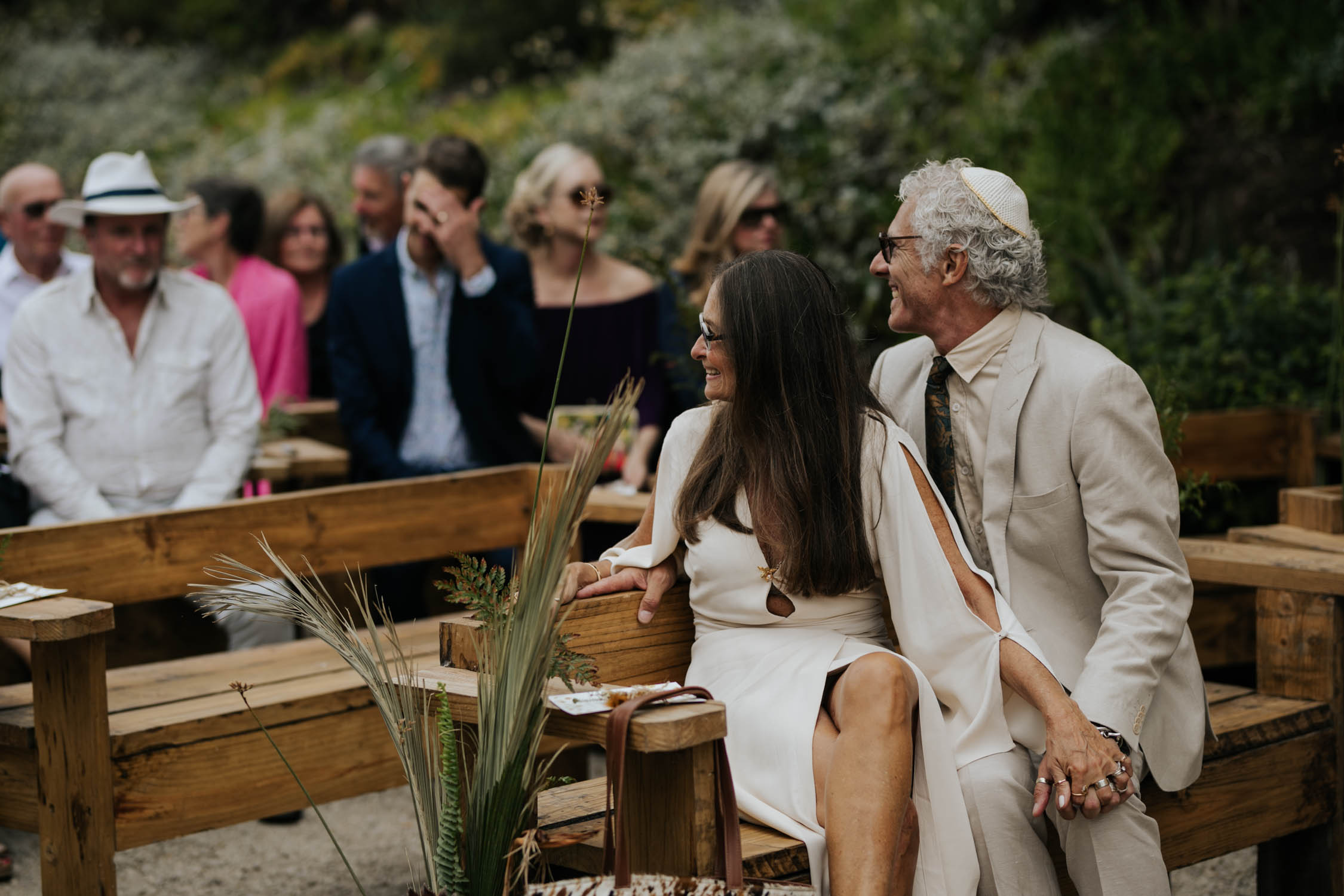 Emotional photo of groom's parents watch their soon to be daughter in law walk down the aisle
