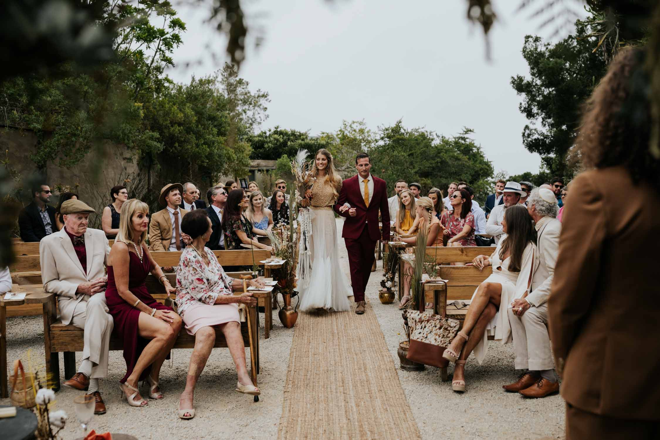 Boho bride carrying dried flower and feather woven macrame wedding bouquet walks down grass carpet aisle at Emily Moon in outside wedding ceremony
