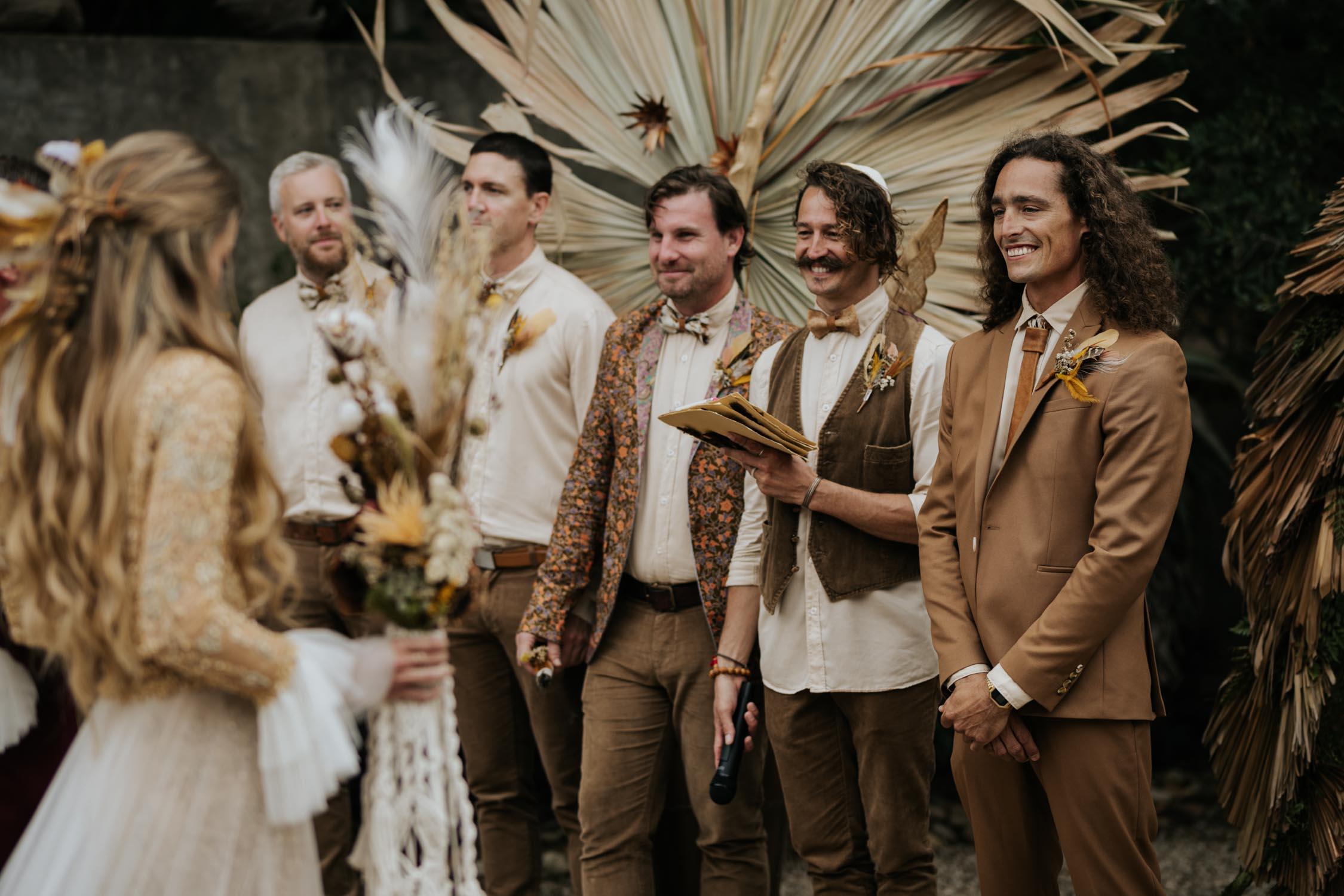 Groom wearing brown suite, beige shirt, brown Nguni cowhide tie, felt hat and foraged dried flowers and feather boutineer watches bride walk down aisle