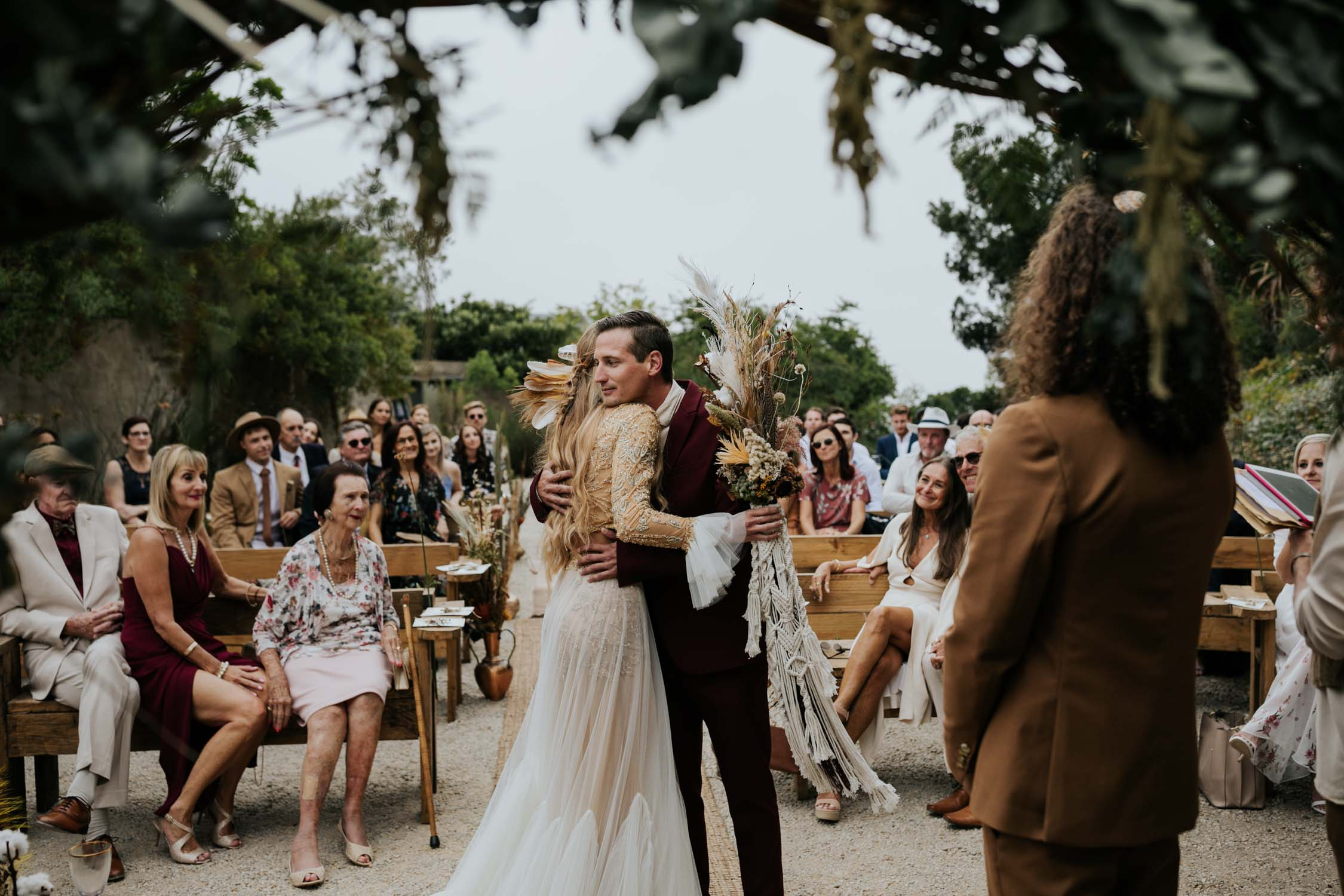 Boho bride hugs brother at top of the aisle