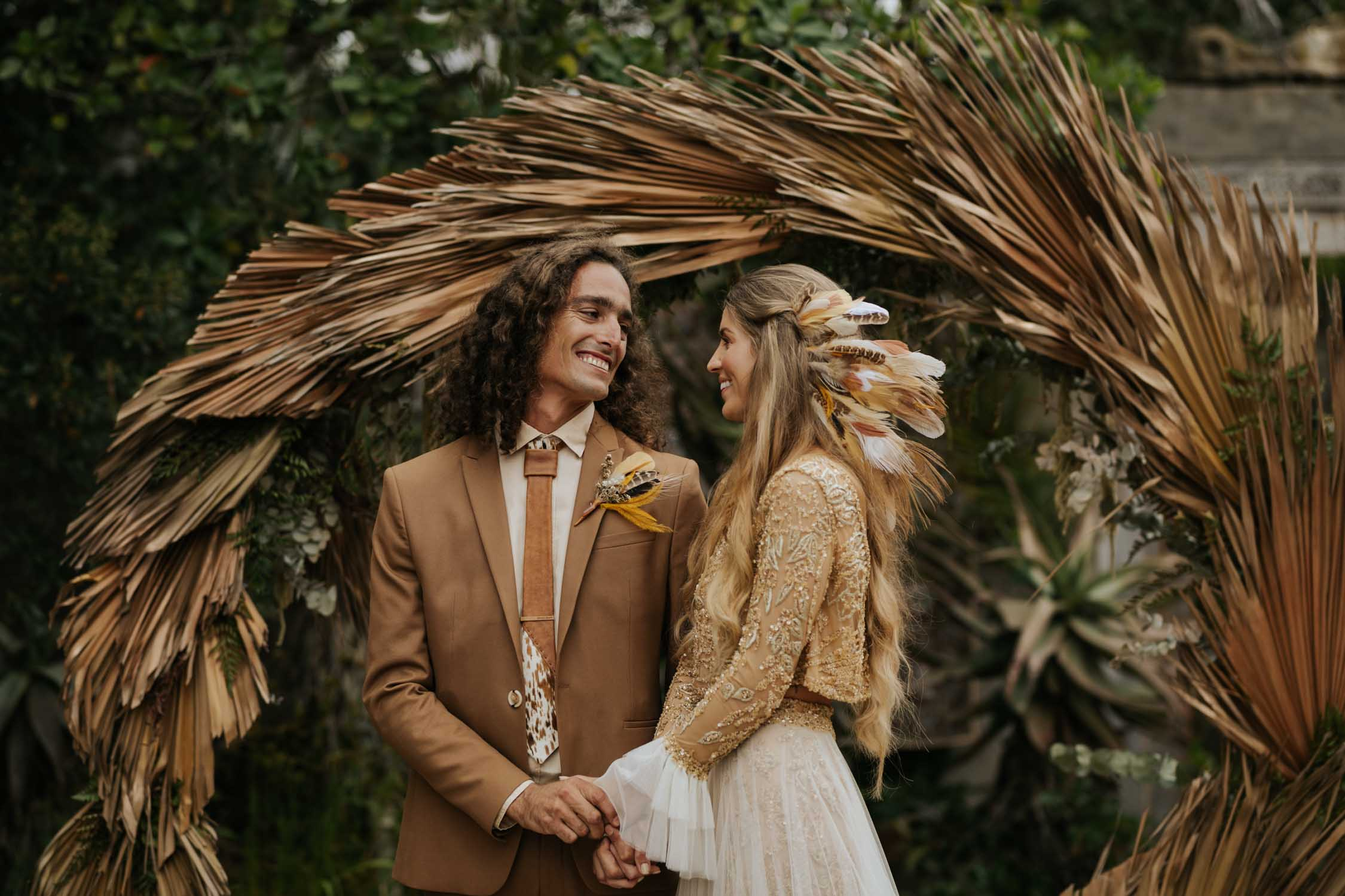 Beautiful boho bride and groom stand in front of trending dried grass wedding arch
