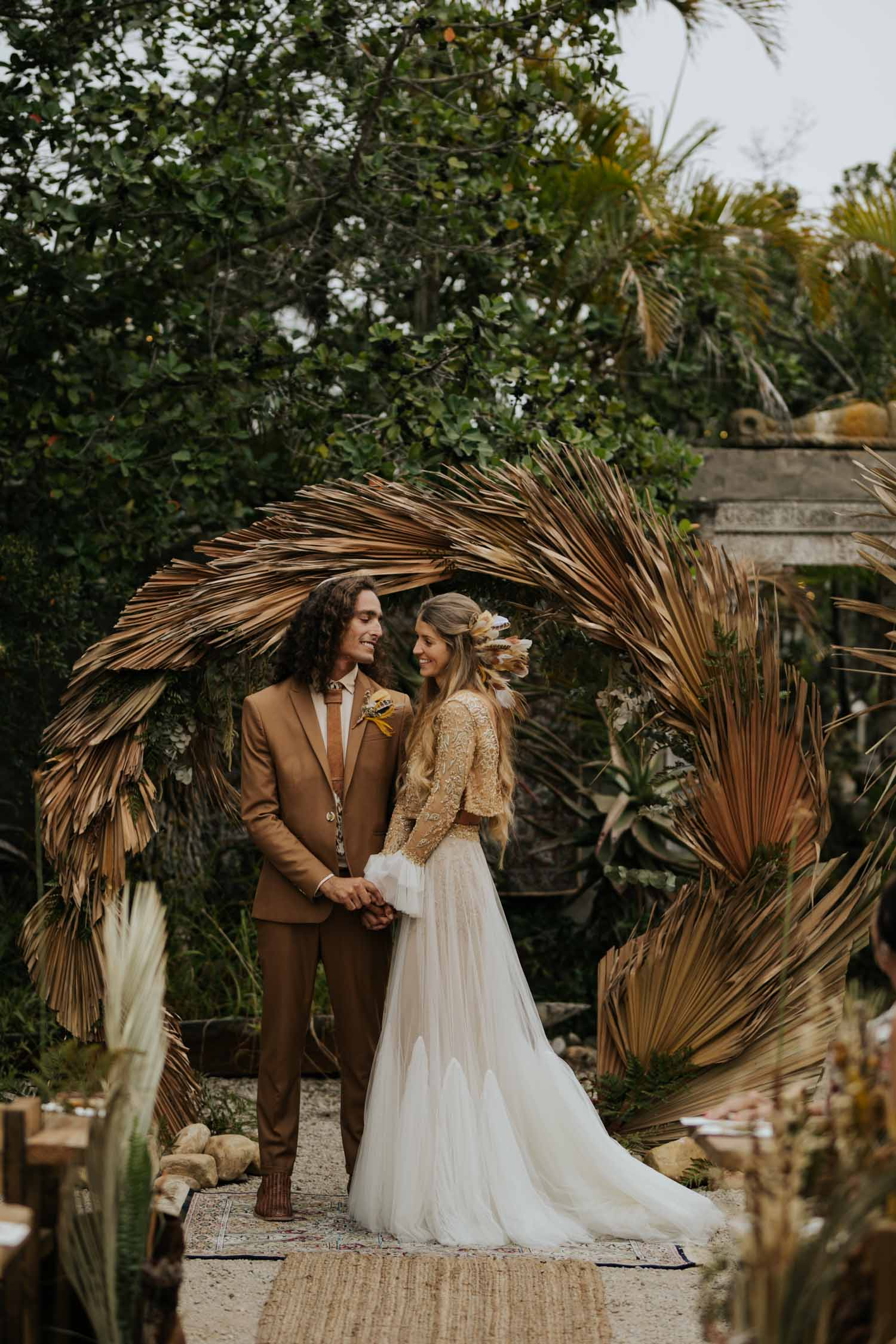 Beautiful boho gypsy bride with feather in her hair and groom stand in front of trending dried grass wedding arch