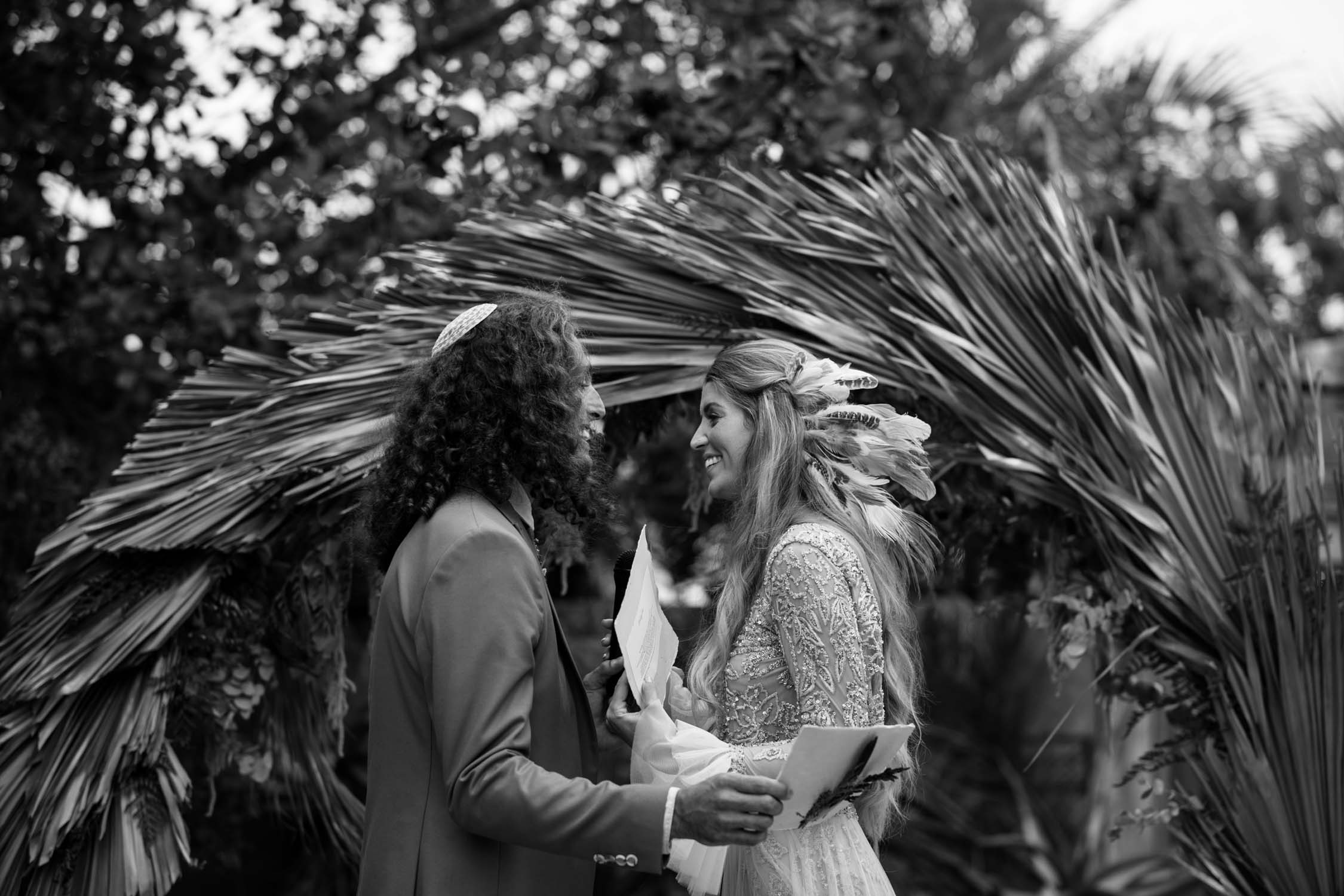 Incredible gorgeous long curly haired bohemian gypsy bride and groom say their vows in front of dried grass circle wedding arch