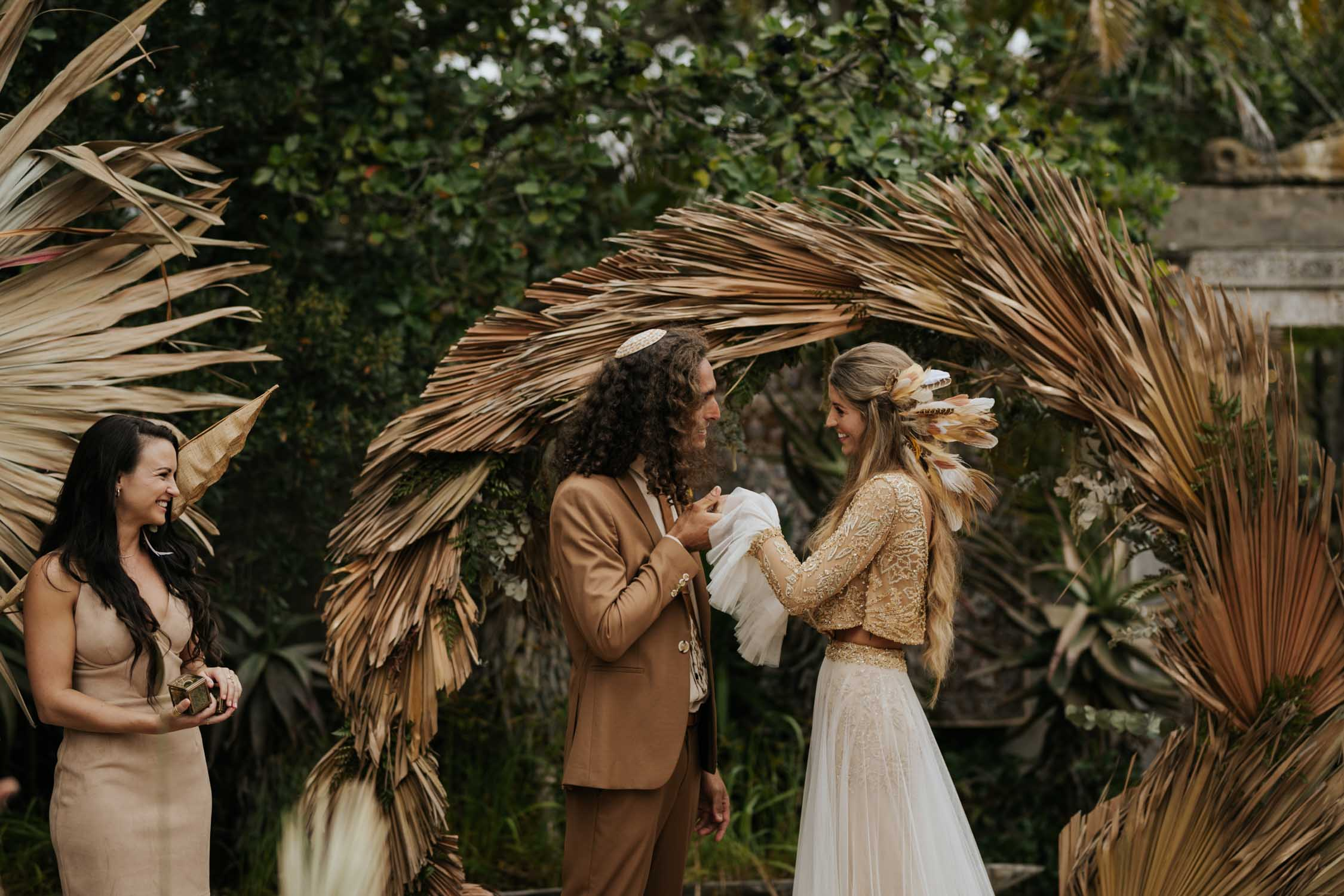 Incredible gorgeous long curly haired bohemian gypsy bride and groom exchange rings in front of dried grass circle wedding arch at Emily Moon, Plett Wedding Venue