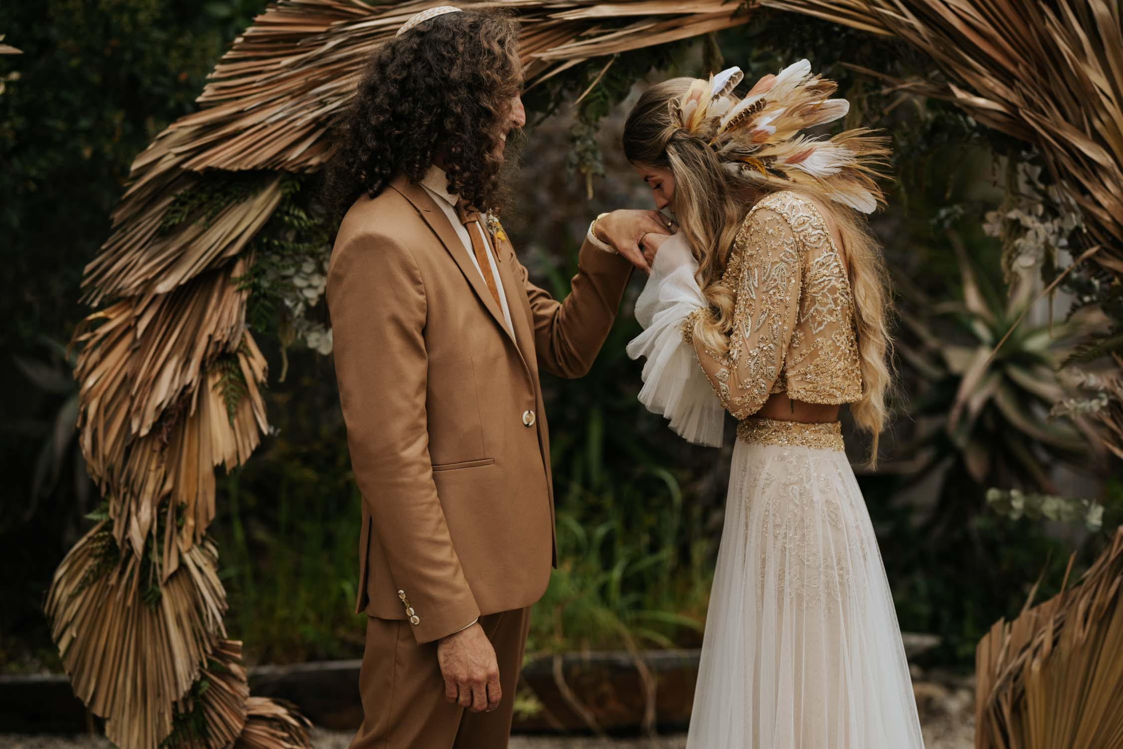Incredible gorgeous long curly haired bohemian gypsy bride kisses groom's hand in front of dried grass circle wedding arch at Emily Moon, Plett Wedding Venue