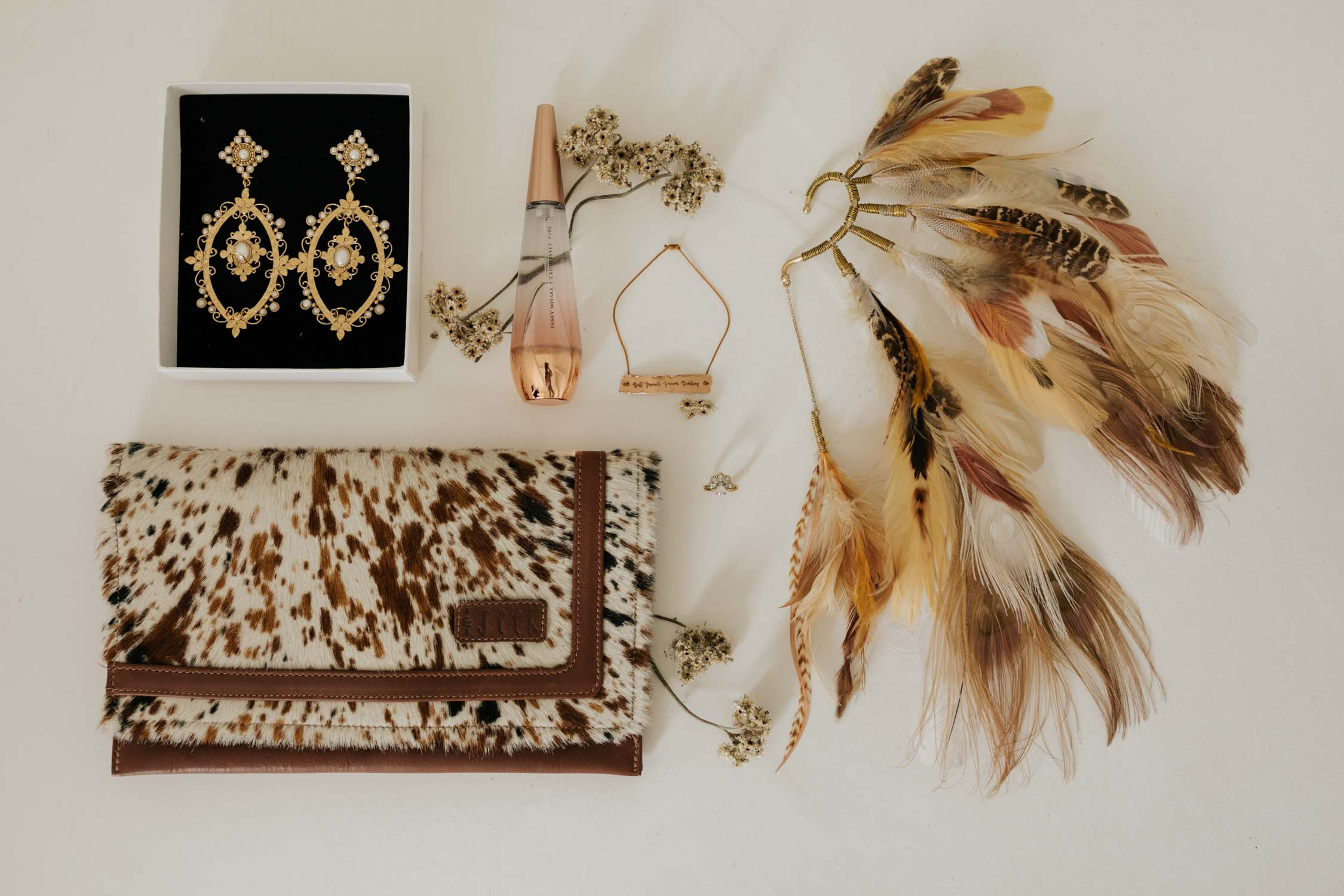 Boho bride flatlay with cowhide clutch bag, feather ear cuff and Bo and Luca earrings