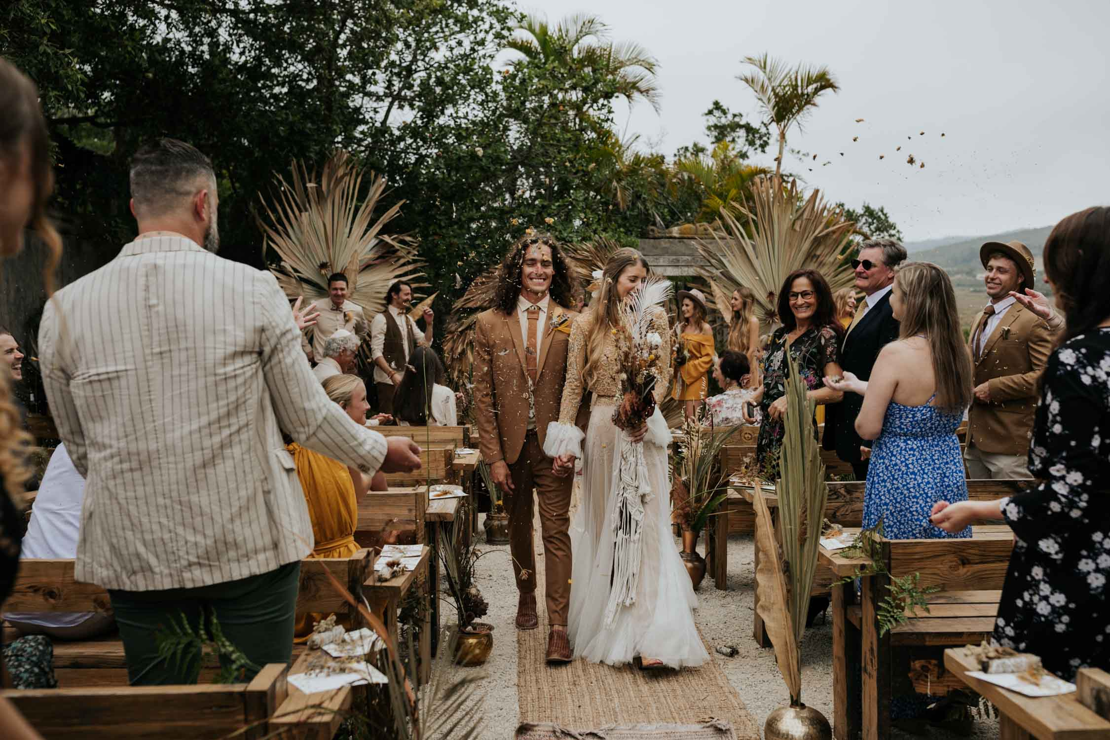 Confetti toss with dried flowers and feather at bohemian wedding at Emily Moon River Lodge in Plett