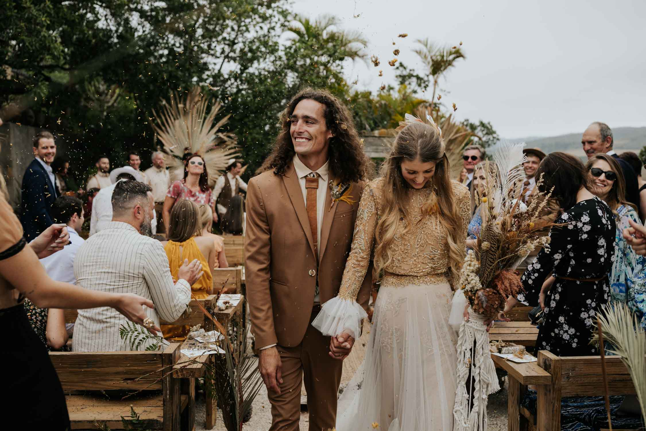 Joyful and fun wedding confetti toss with dried flowers and feather at bohemian wedding at Emily Moon River Lodge in Plett