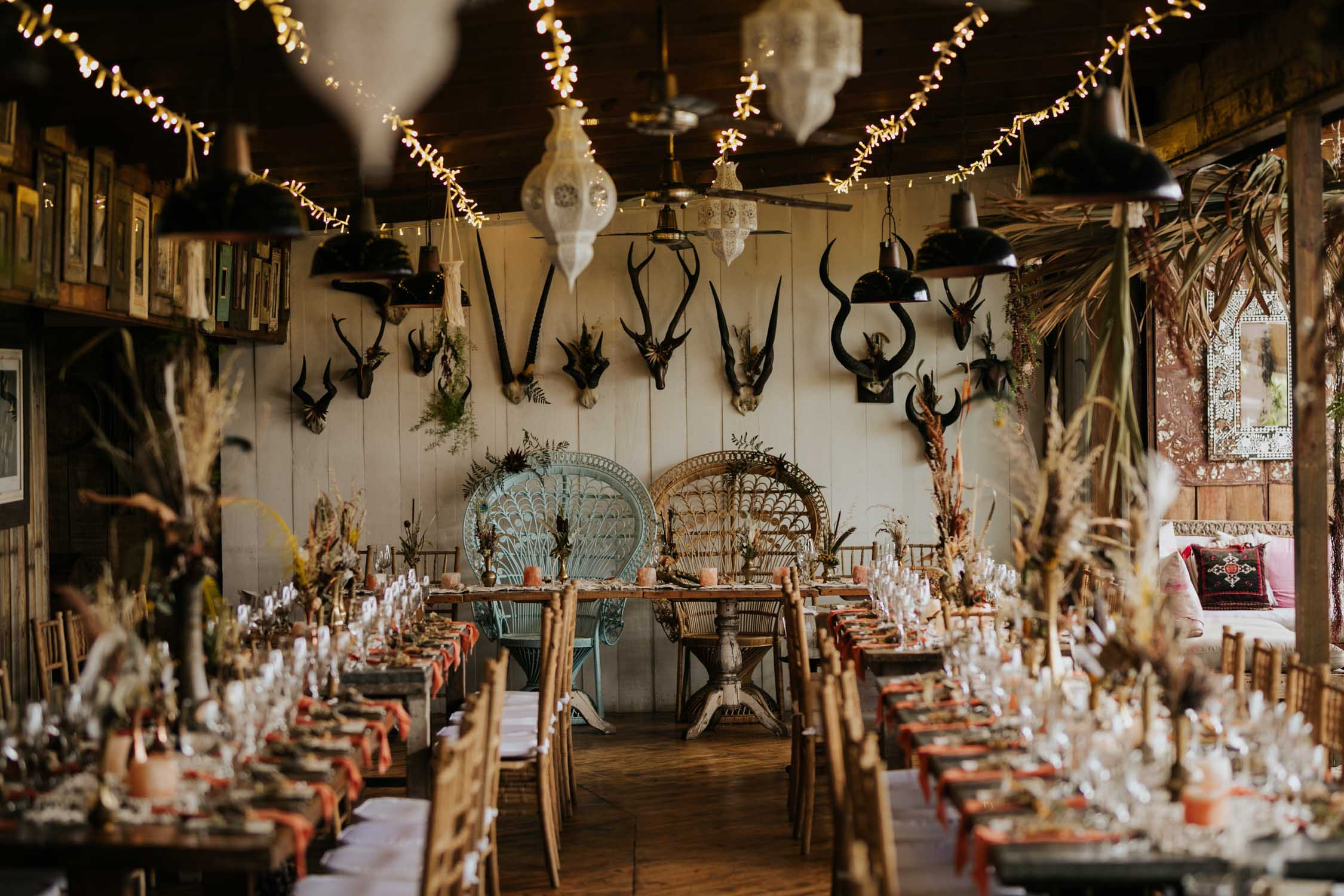 Boho inspired wedding decor of rustic wooden chairs, woven macrame table runners, feather and dried flower arrangements, skull table numbers, gemstones and Bali Wicker Peacock Chairs