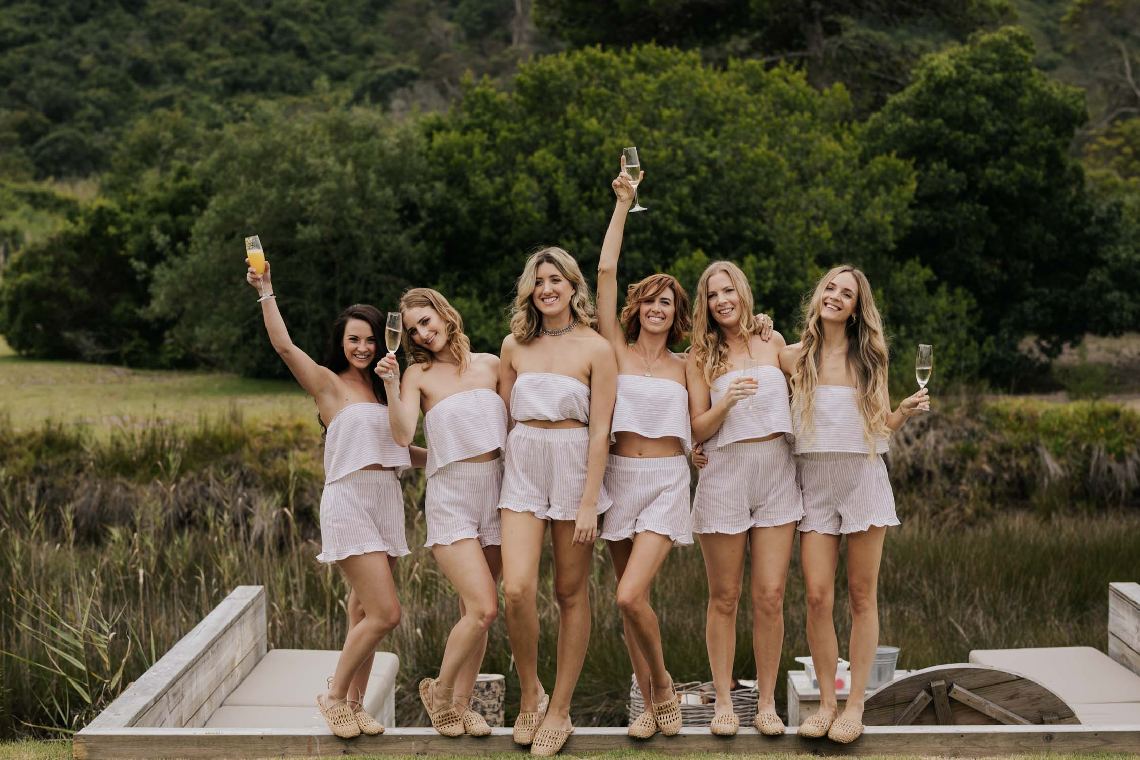 Bridesmaids drink champagne in their boho striped matching PJs while getting ready from wedding at Emily Moon in Plett