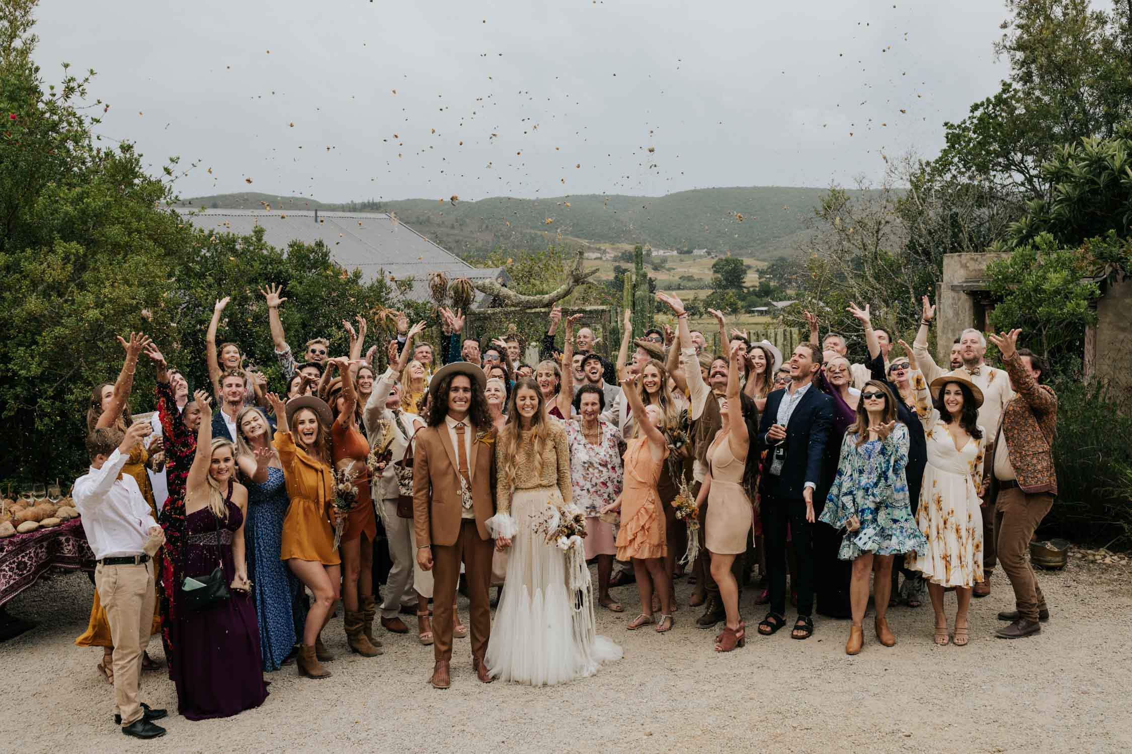 Fun group photo of all the guests at wedding throwing confetti