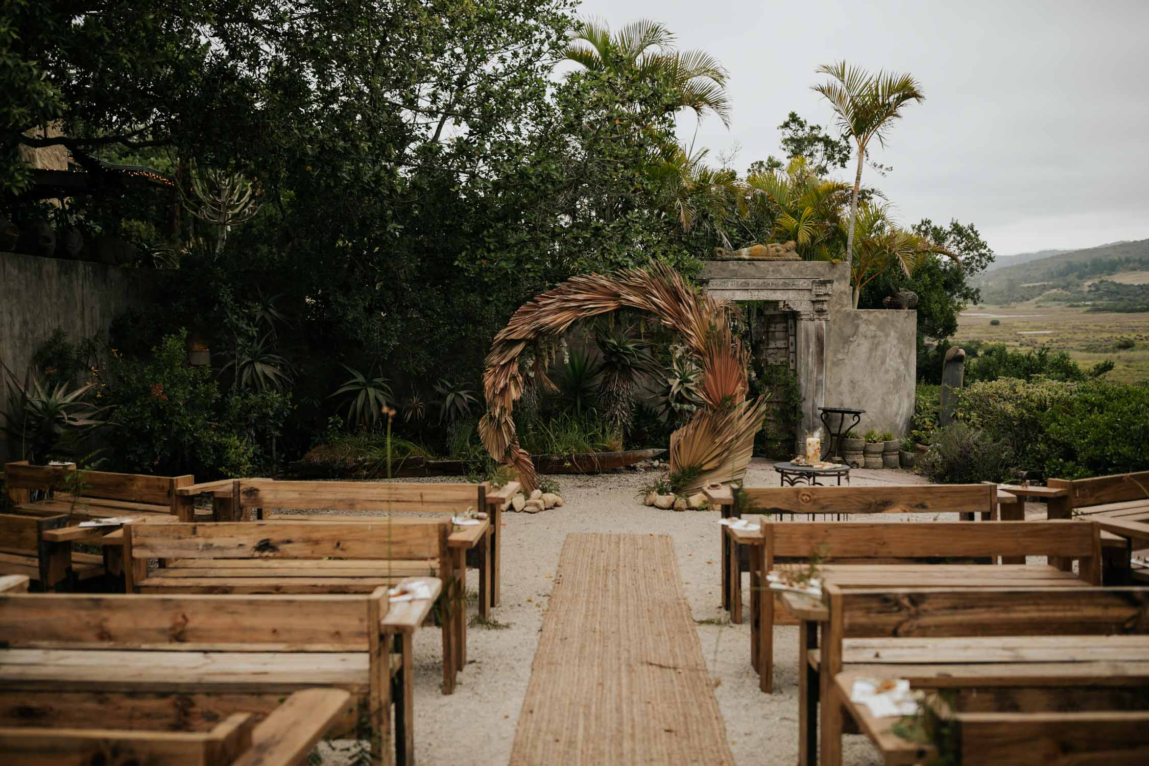 Boho neutral colours ceremony setup with dried leaf circle arch and wooden benches at Emily Moon