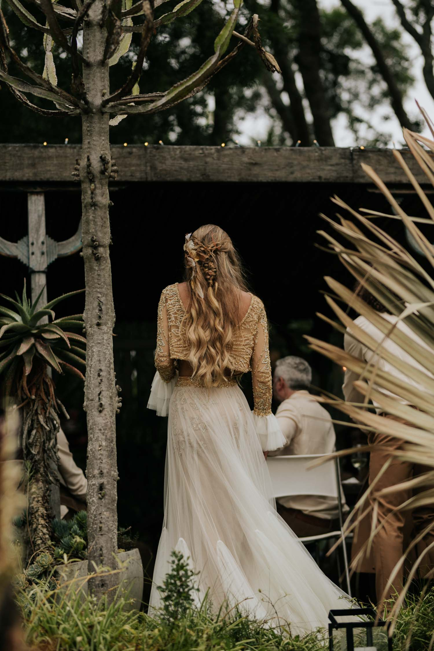 Boho bride wears feather ear cuff and hair piece and a wedding dress with flared long sleeves, sheer skirt, gold detailed top and messy plait in hair at Emily Moon