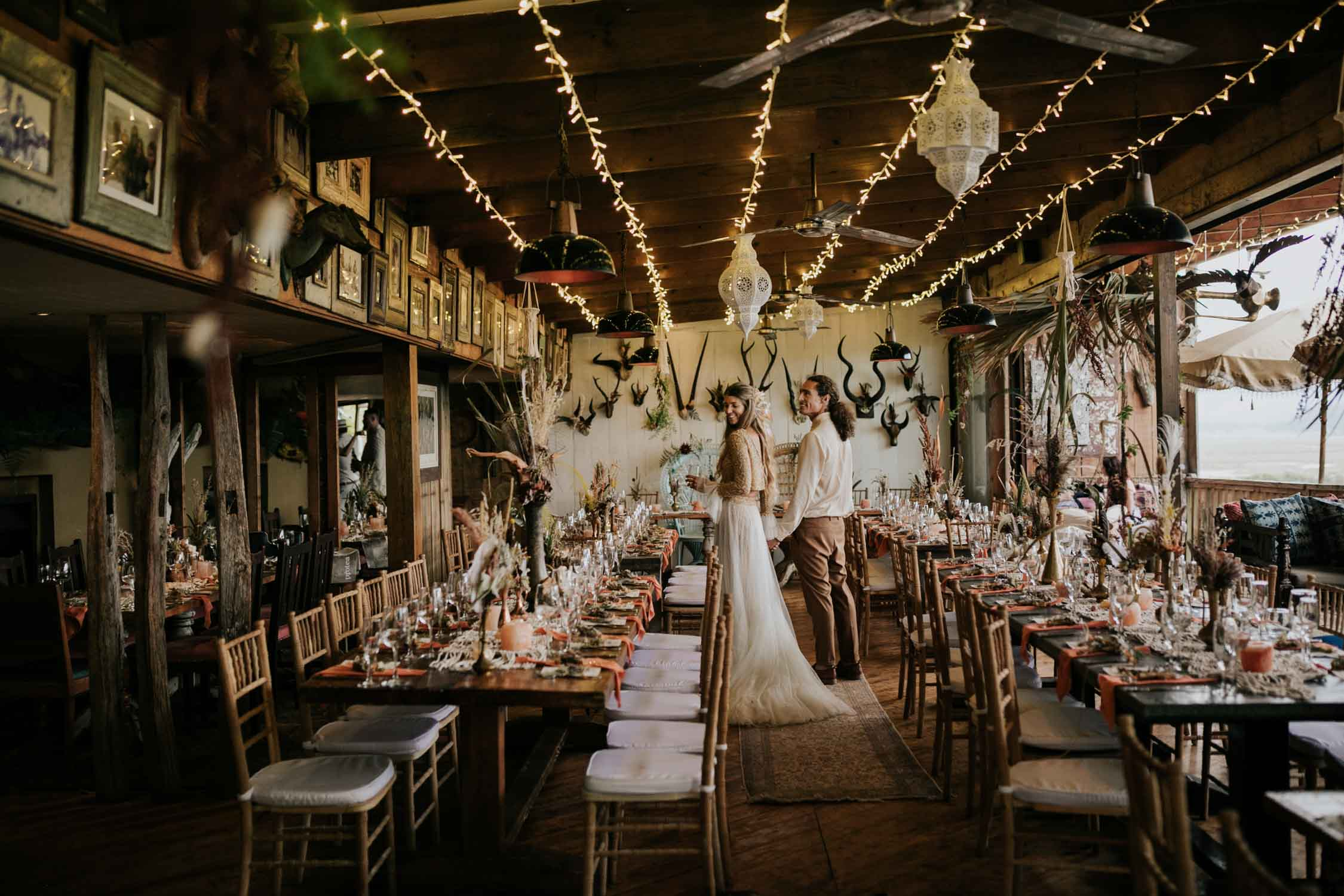 Boho inspired wedding decor of rustic wooden chairs, woven macrame table runners, feather and dried flower arrangements in brass and copper pots, skull table numbers, gemstones and Bali Wicker Peacock Chairs at destination wedding in Cape Town South Africa