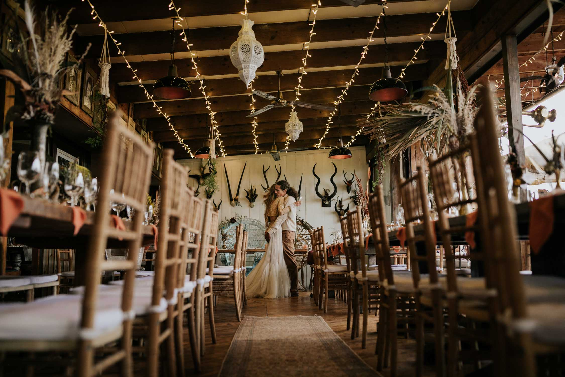 Boho inspired wedding decor of rustic wooden chairs, woven macrame table runners, feather and dried flower arrangements in brass and copper pots, skull table numbers, gemstones and Bali Wicker Peacock Chairs at destination wedding in Plett South Africa