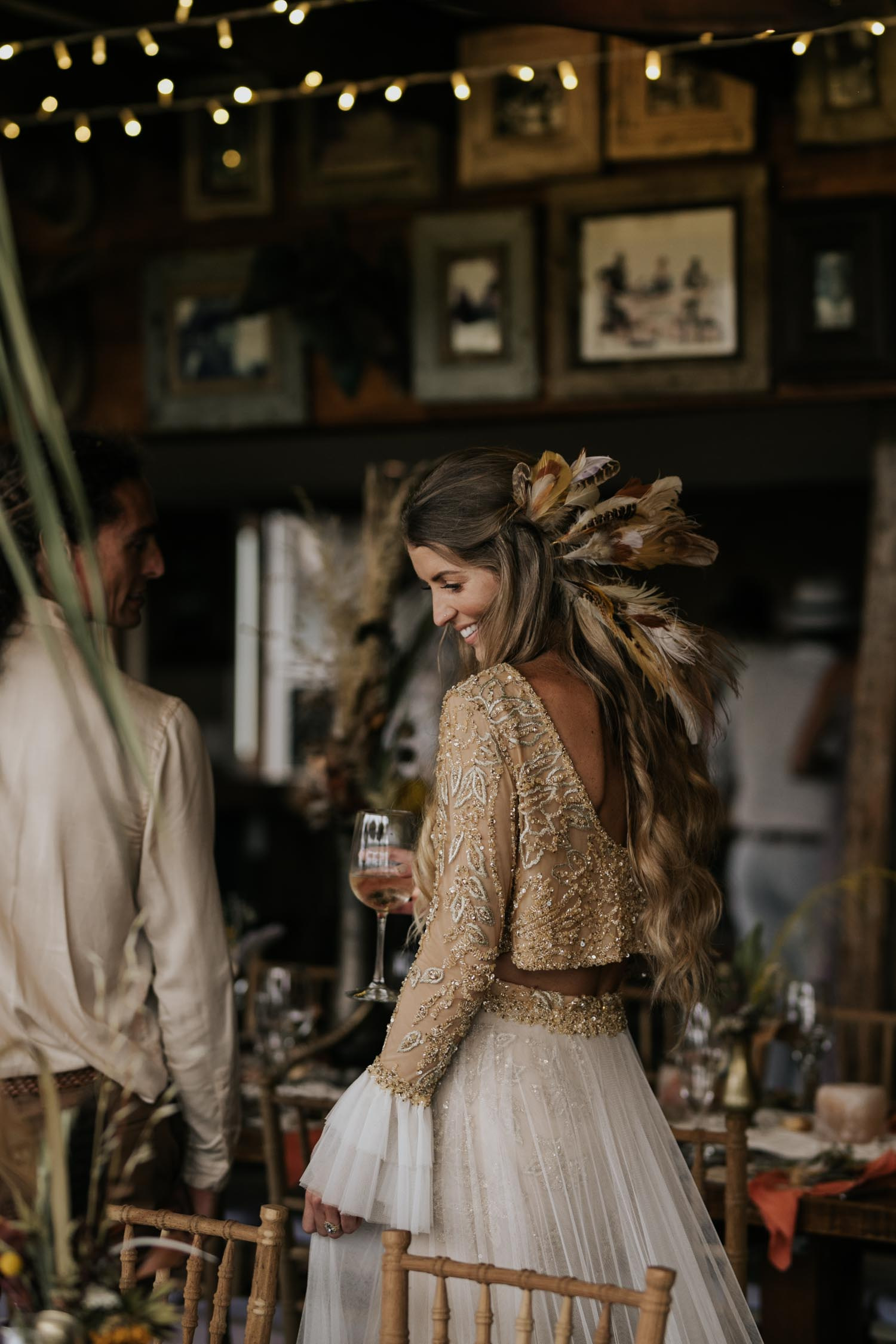 Breathtaking boho gypsy bride with feather in her hair smiles seeing the beauty of her reception decor