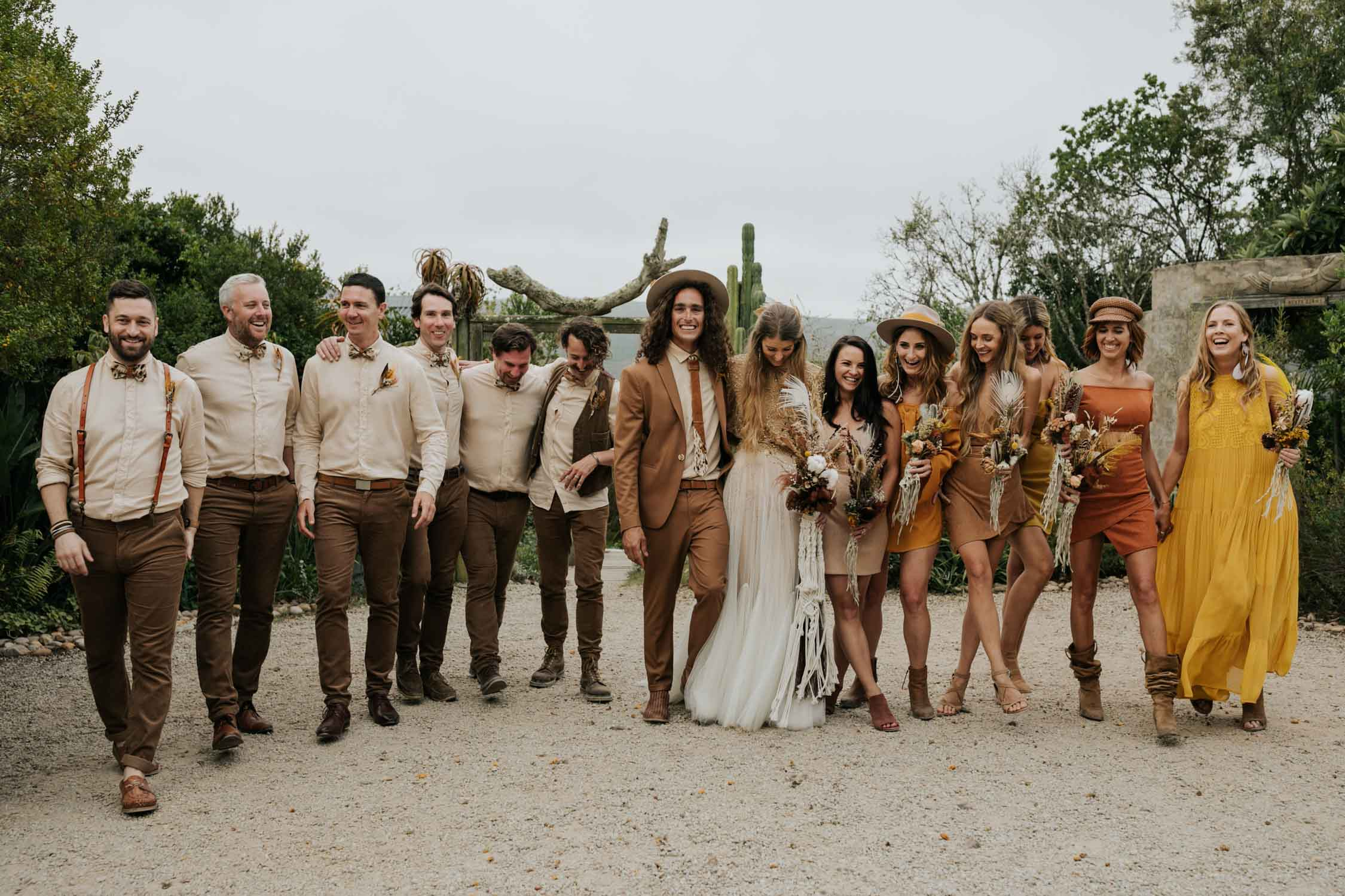 The ultimate boho gypsy bridal party wearing gypsy sunshine and rust coloured dresses, hats and brown suits in front of cactus at Emily Moon