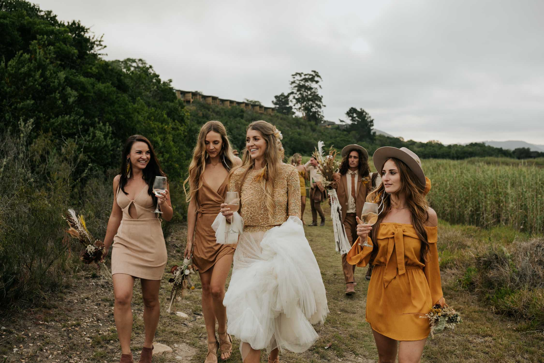 The ultimate boho gypsy bride tribe goals wearing gypsy sunshine and rust coloured dresses and hats