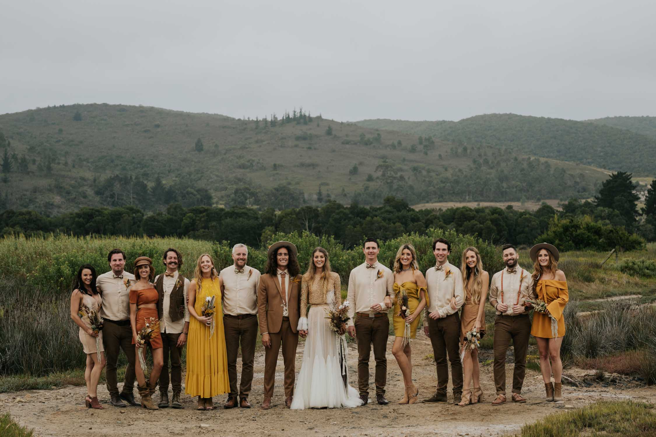 The ultimate boho gypsy bridal party wearing gypsy sunshine and rust coloured dresses, hats and brown suits in at destination wedding in Vancouver