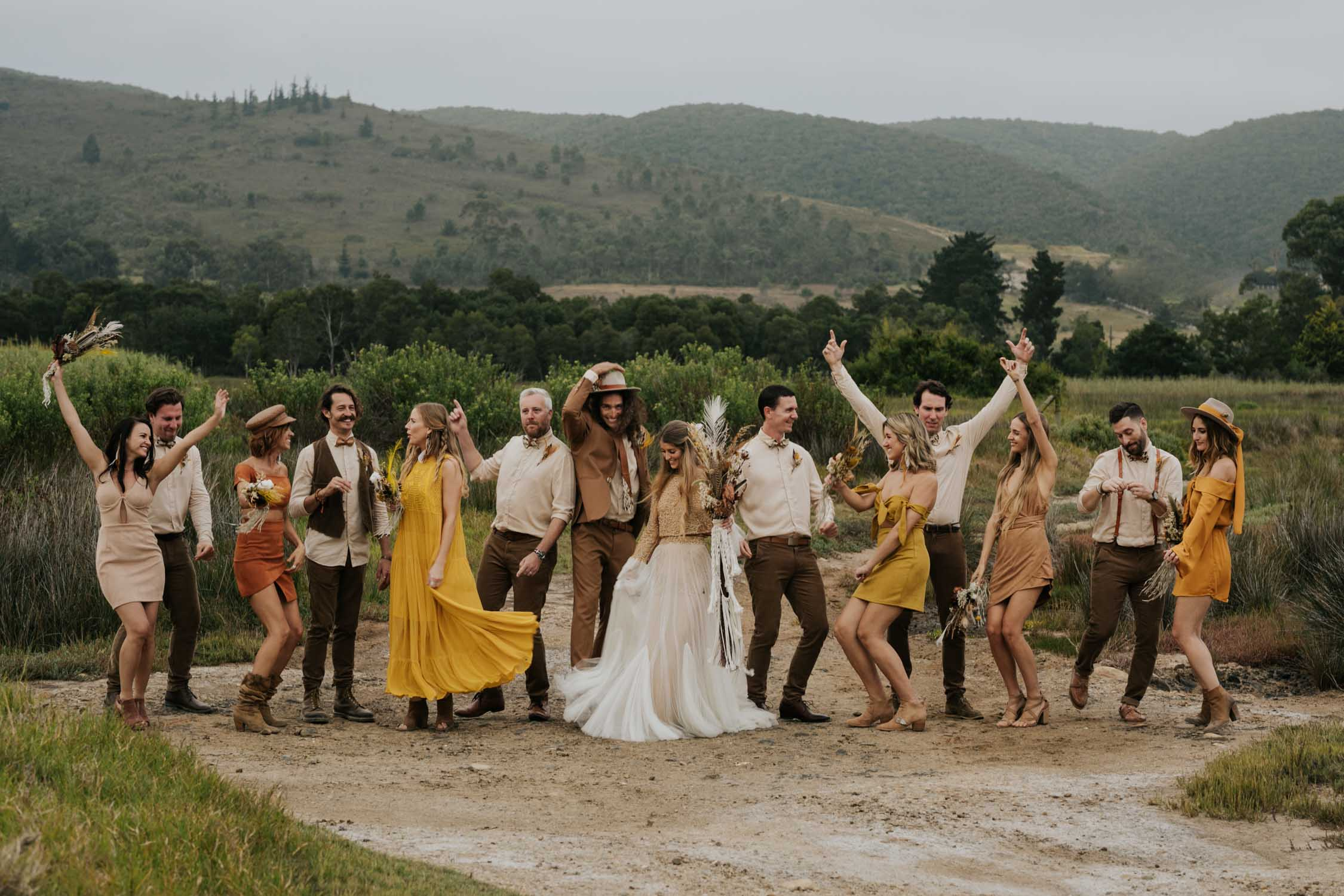The ultimate boho gypsy bridal party wearing gypsy sunshine and rust coloured dresses, hats and brown suits dance wildly at wedding in Vancouver