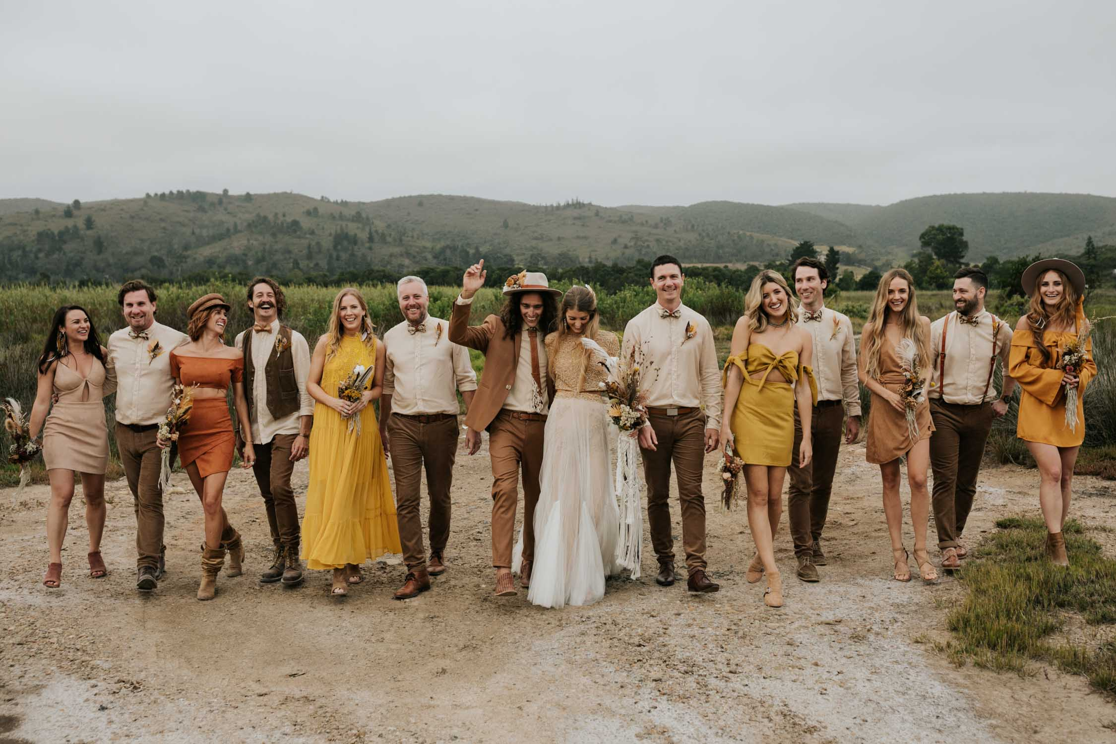 The ultimate boho gypsy bridal party wearing gypsy sunshine and rust coloured dresses, hats and brown suits in at destination wedding in Plett South Africa