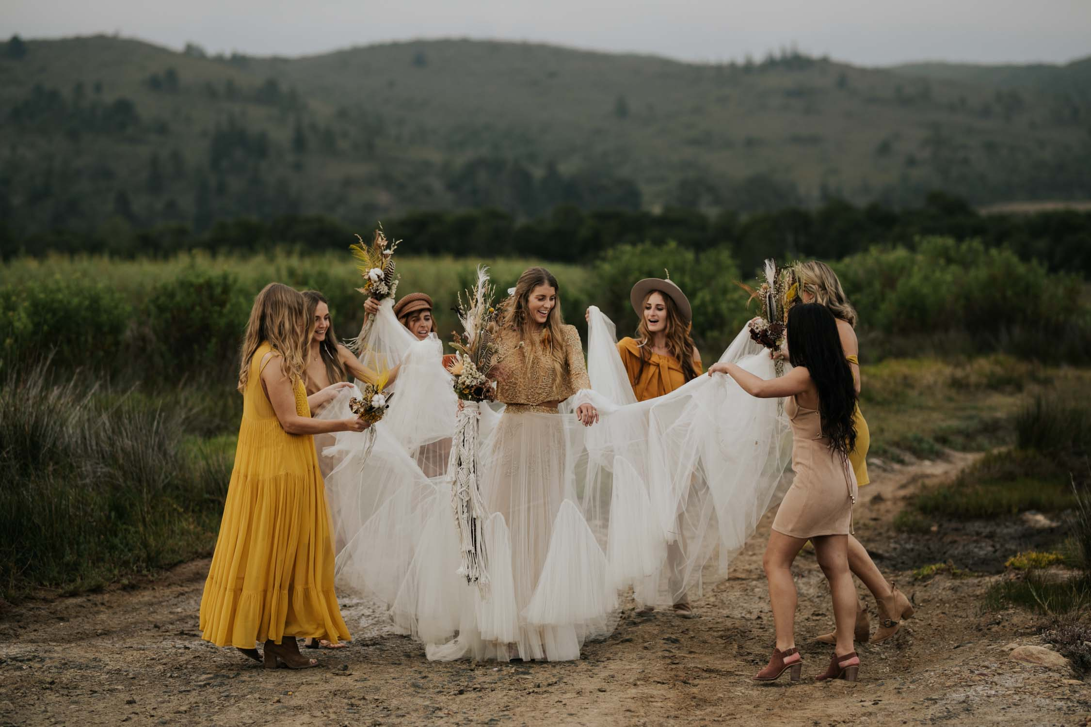 The ultimate boho gypsy bride tribe wearing gypsy sunshine and rust coloured dresses and hats and dance wildly