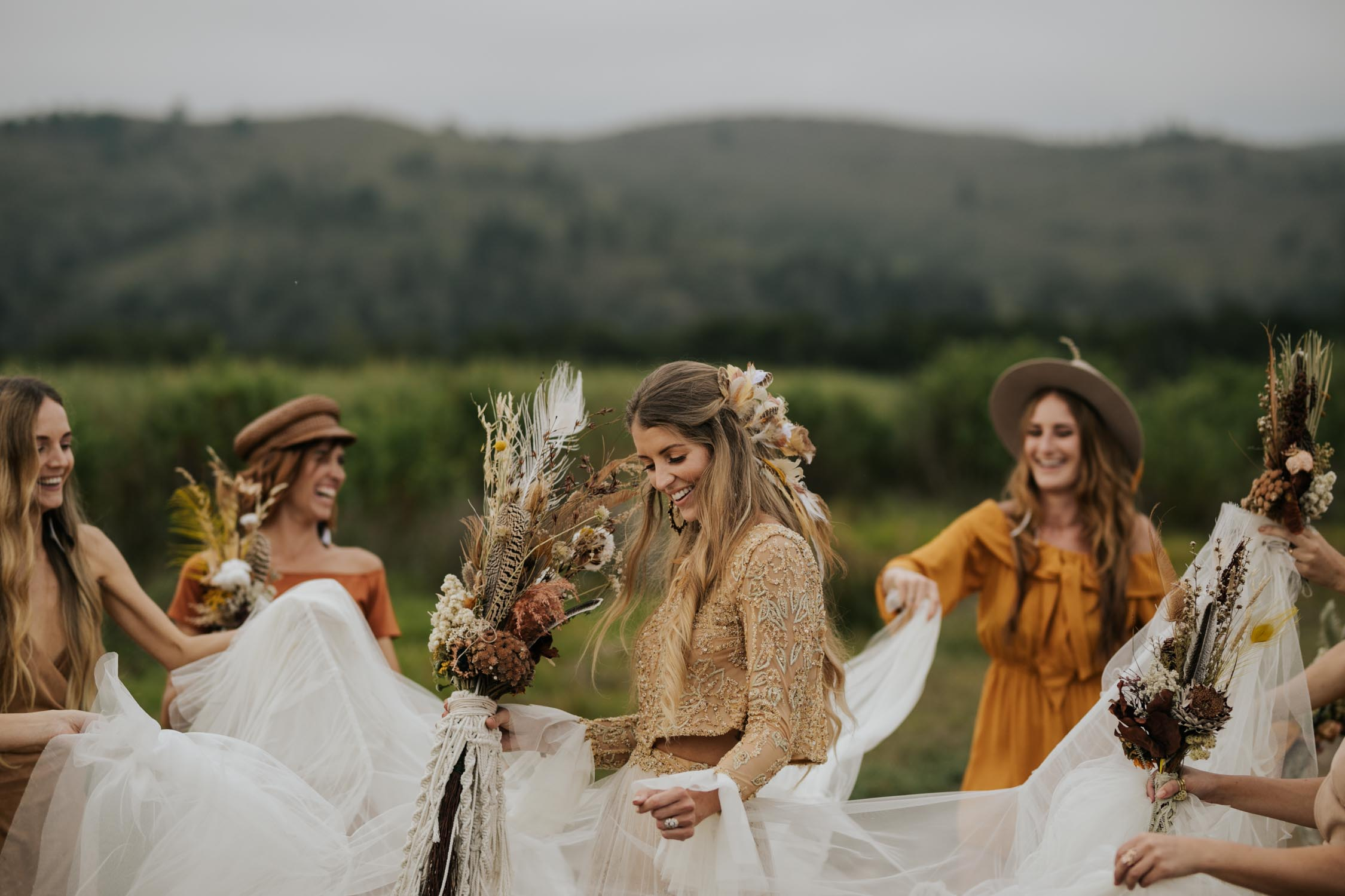 The ultimate boho gypsy bridesmaids wearing gypsy sunshine and rust coloured dresses and hats dance with beautiful bride