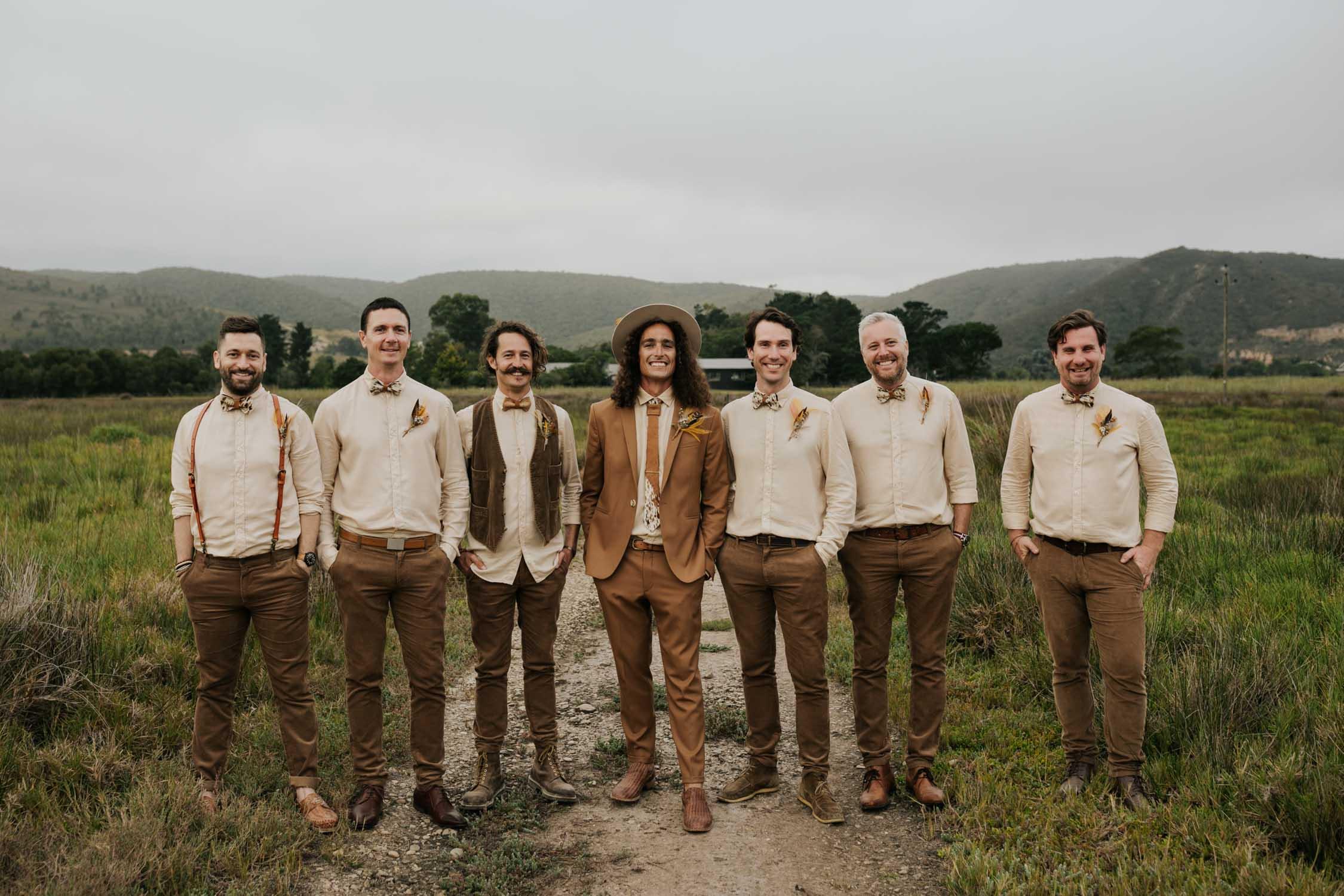 Groom and groomsmen wear brown suites, beige shirts, brown Nguni cowhide bowties, felt hat and foraged dried flowers and feather boutineers