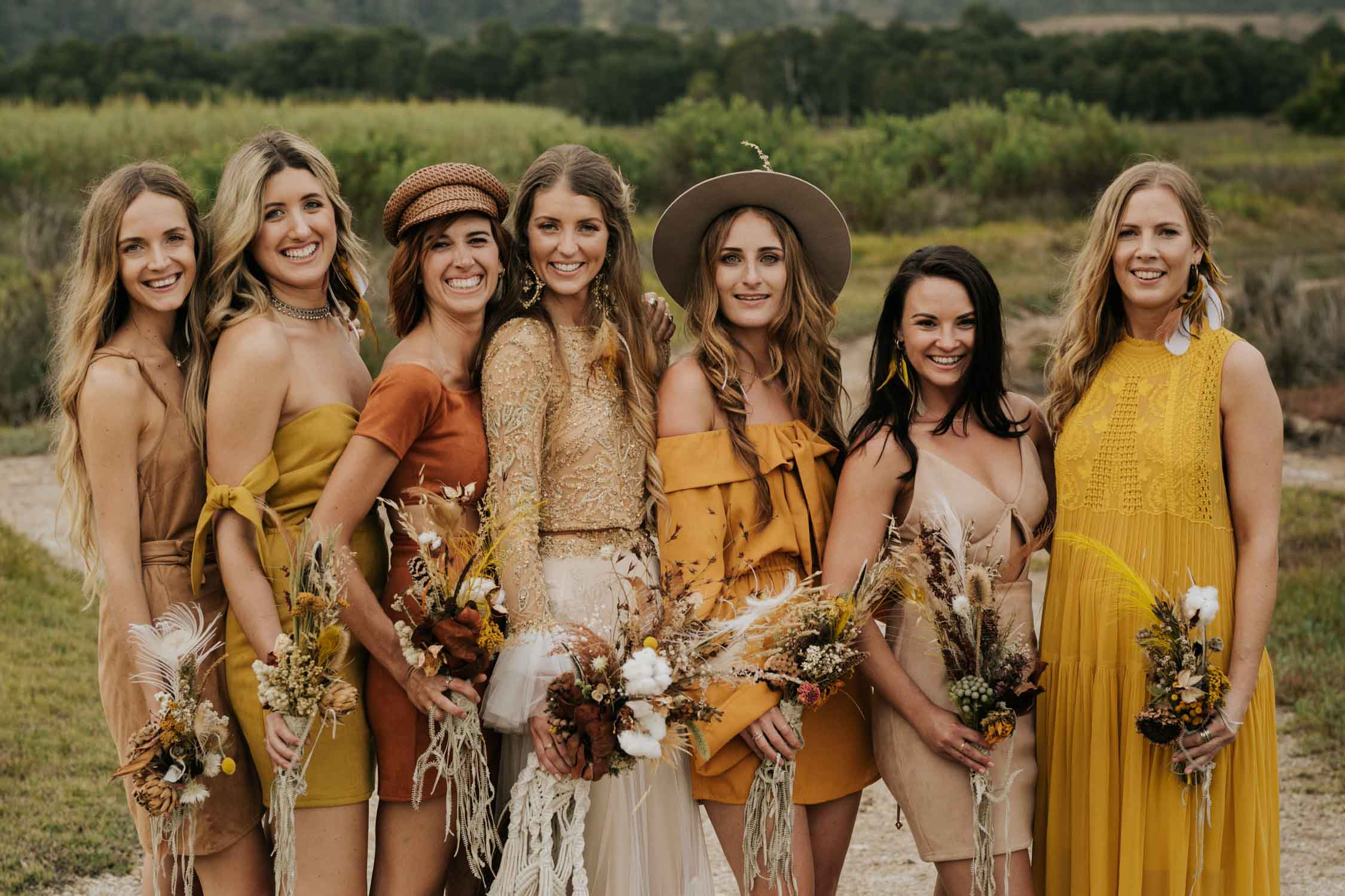 The ultimate boho gypsy bride tribe wearing gypsy sunshine, orange, yellow and rust coloured dresses, hats and leather boots