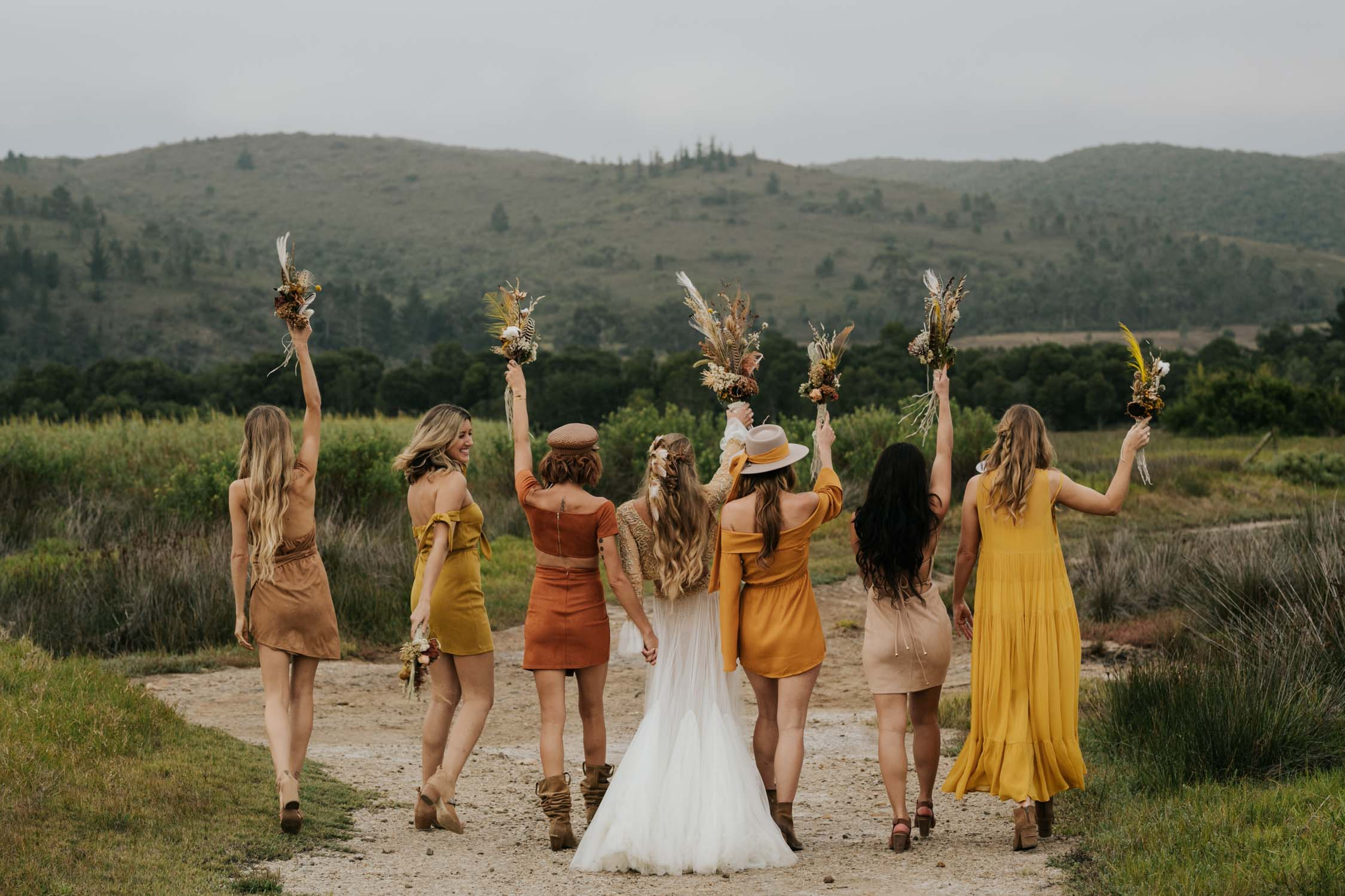 The ultimate boho gypsy bride tribe wearing gypsy sunshine and rust coloured dresses, hats and leather boots