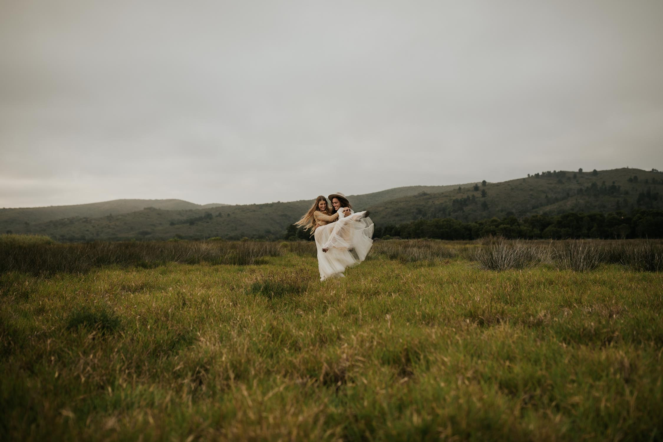 Groom spins boho bride in wild field at Emily Moon River Lodge Wedding