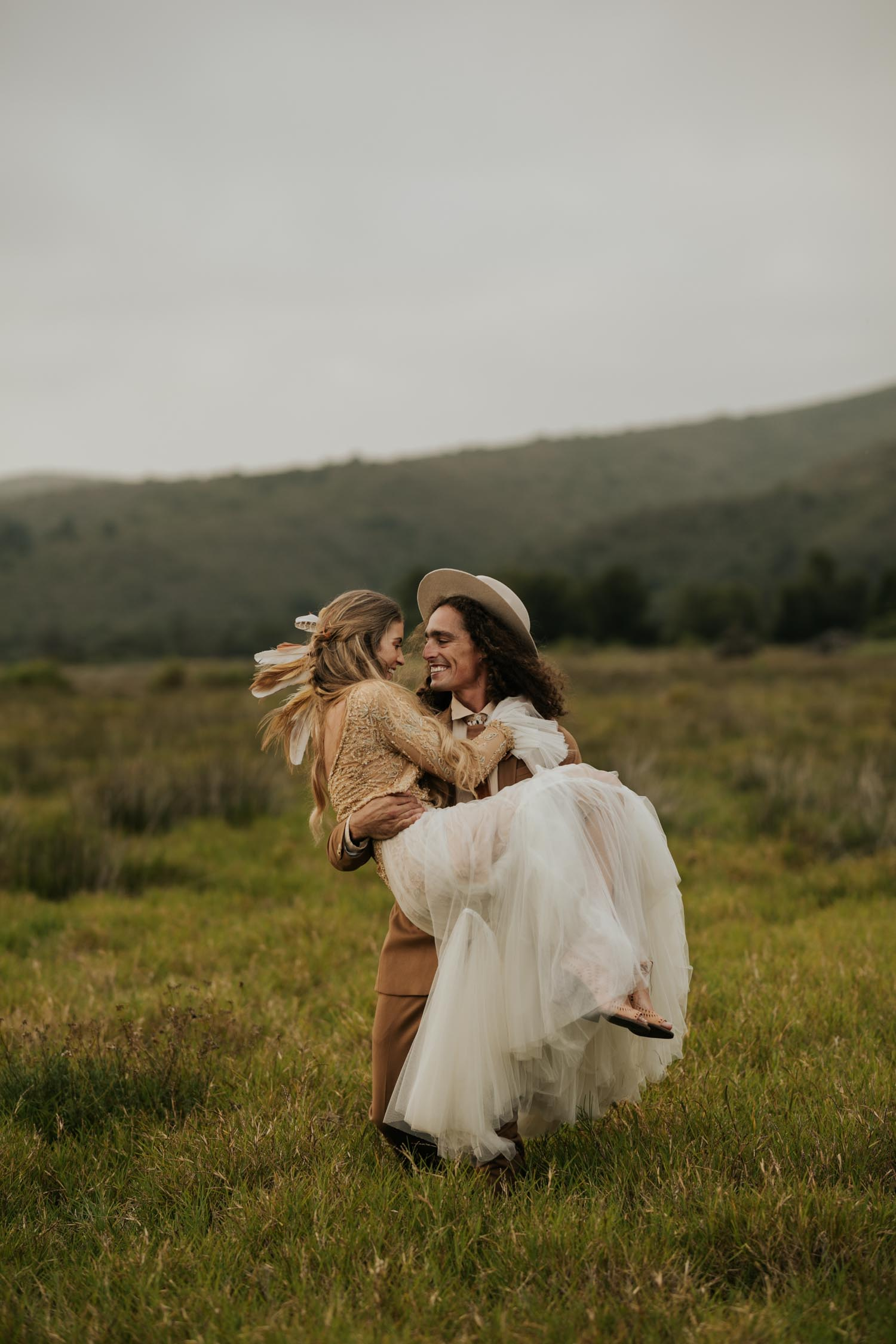 Longhaired curly haired groom wearing felt hat carries boho blonde bride in open field
