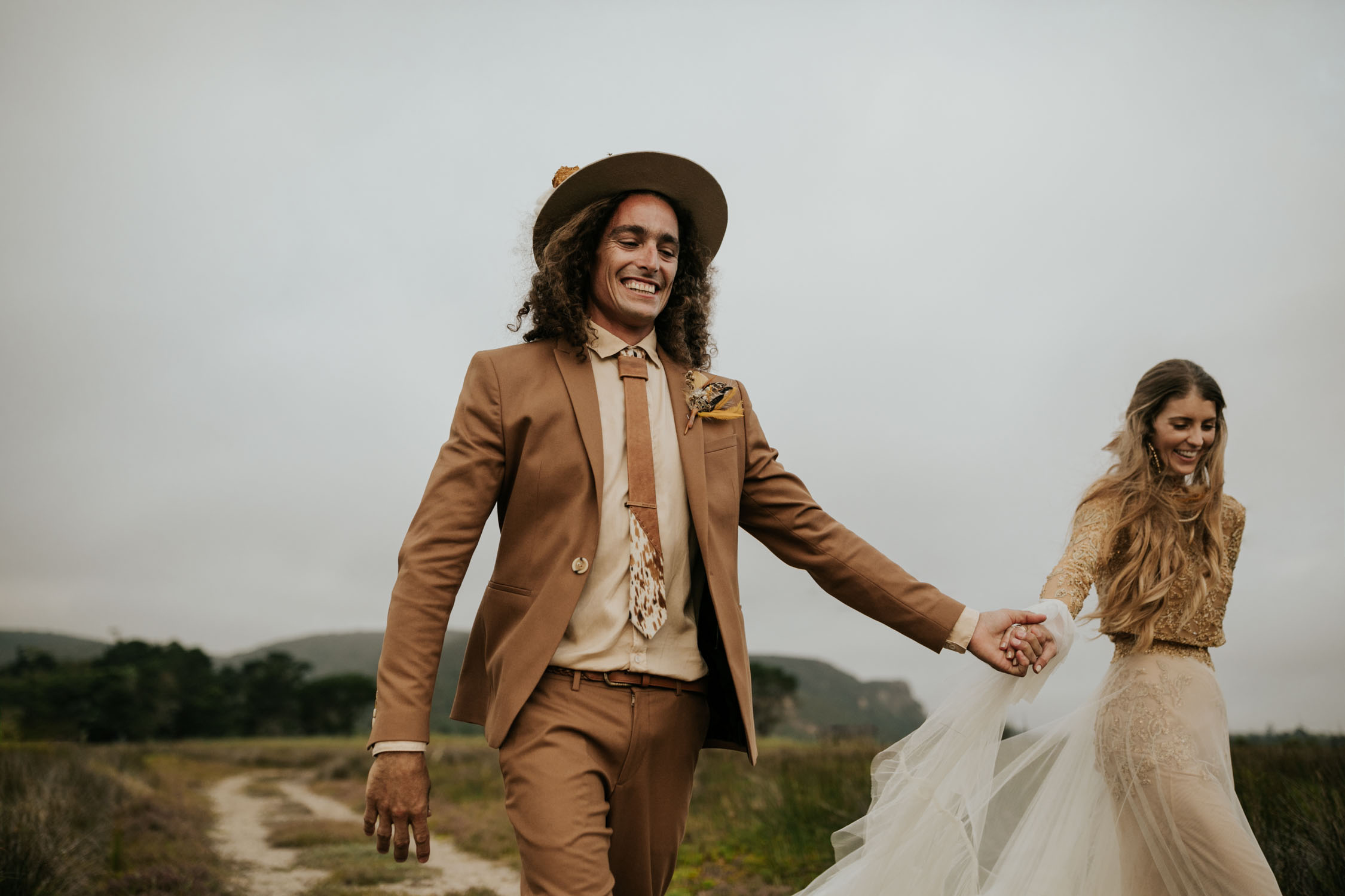 Groom wearing brown suite, beige shirt, brown Nguni cowhide tie, felt hat and foraged dried flowers and feather boutineer holds his bride's hand