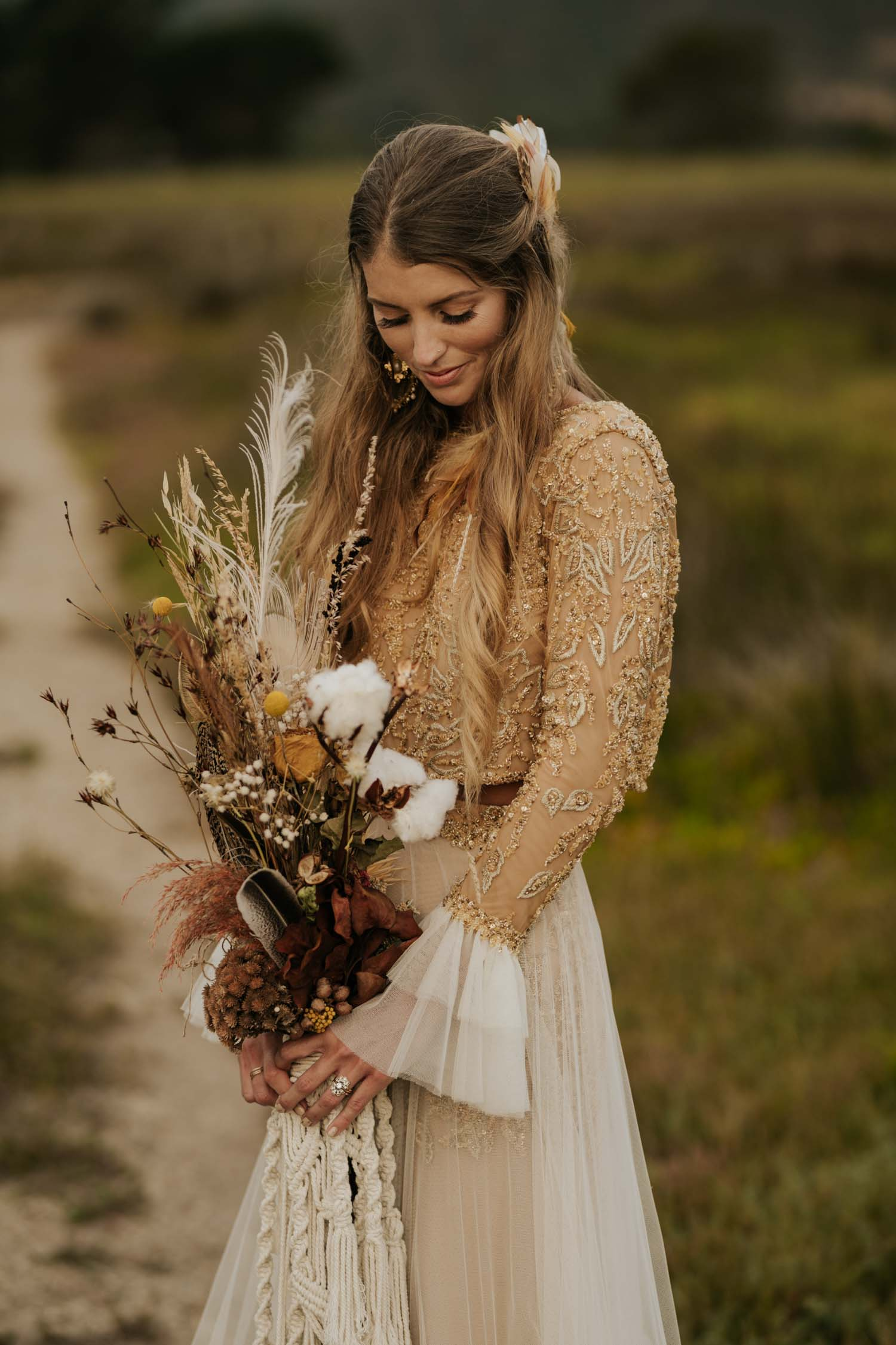 Beautiful boho bride wears feather ear cuff, hair piece and a wedding dress with flared long sleeves, sheer skirt and gold detailed top holds dried flower and feather macrame bouquet in a open field at Vancouver wedding