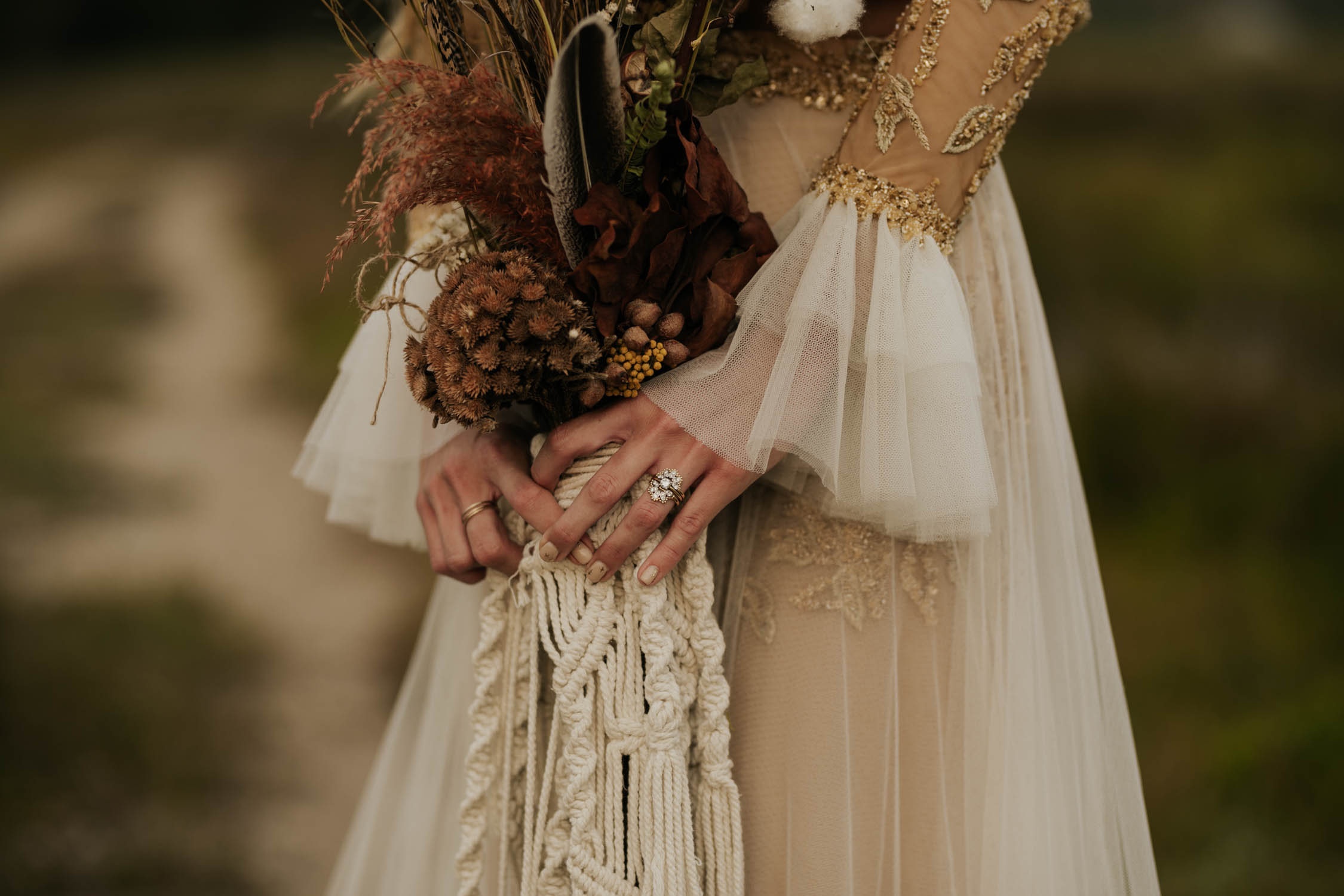 Beautiful boho bride wears feather ear cuff, hair piece and a wedding dress with flared long sleeves, sheer skirt and gold detailed top holds dried flower and feather macrame bouquet