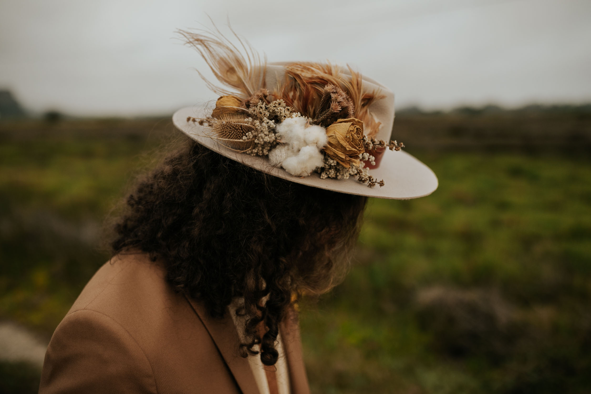 Hipster groom's brown felt hat decorated with natural feathers, foraged dried flowers and cotton