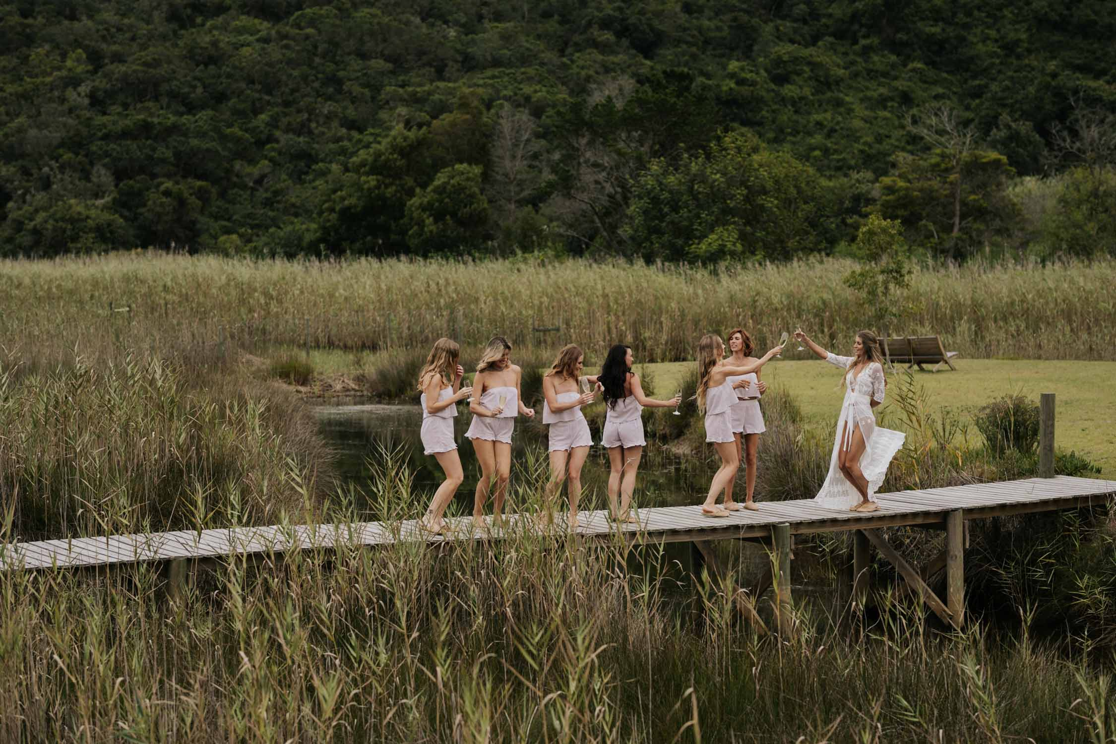 Boho bride with long curly hair dressed in white lace PJs and gown dancing on Emily Moon bridge drinking champagne with her bridesmaids