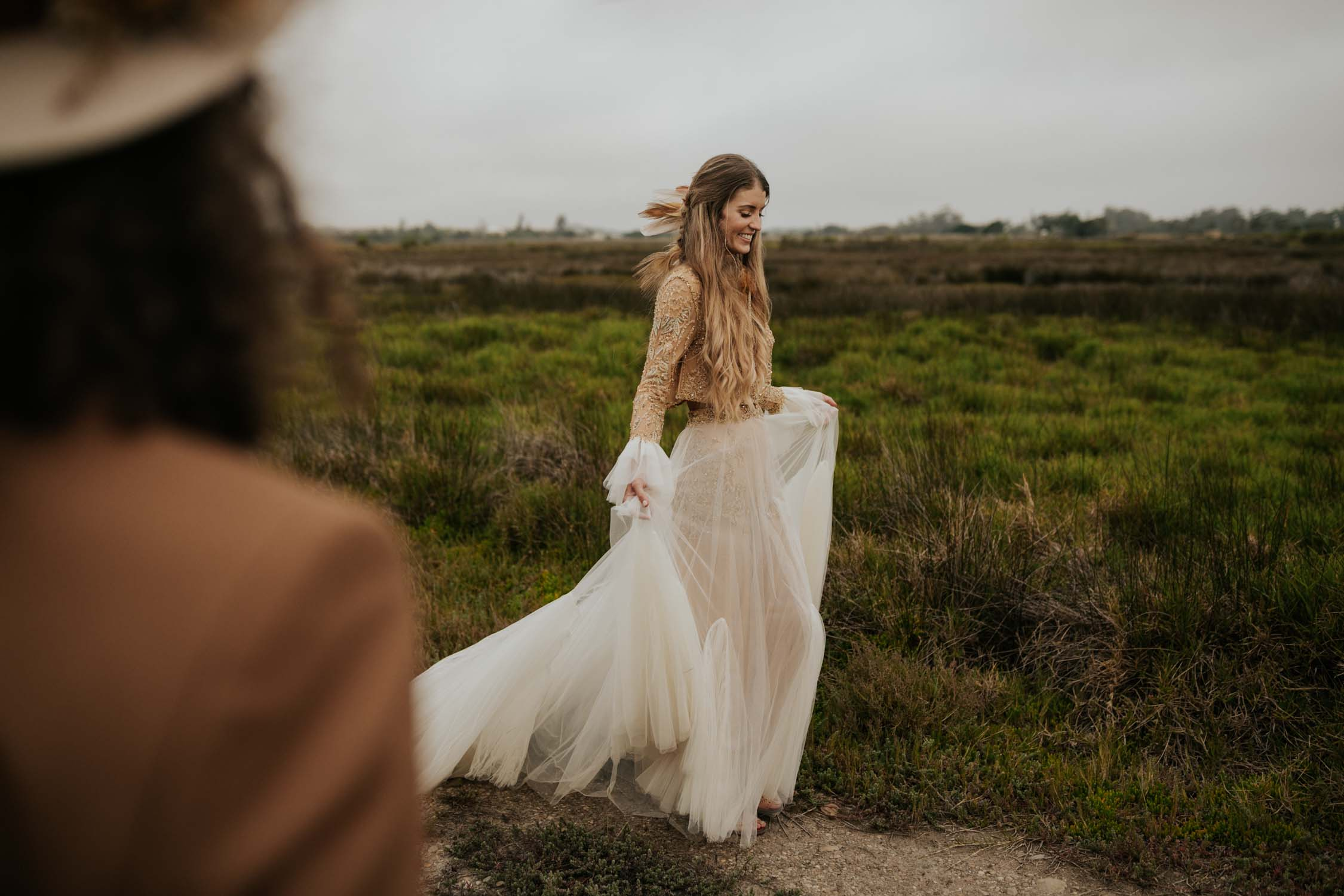 Boho bride wears feather ear cuff and hair piece and a wedding dress with flared long sleeves, sheer skirt and gold detailed top
