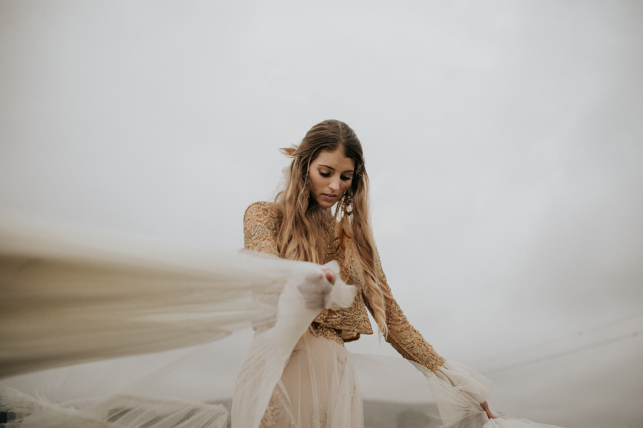 Boho bride wears feather ear cuff and hair piece and a wedding dress with flared long sleeves, sheer skirt and gold detailed top shows off her dress