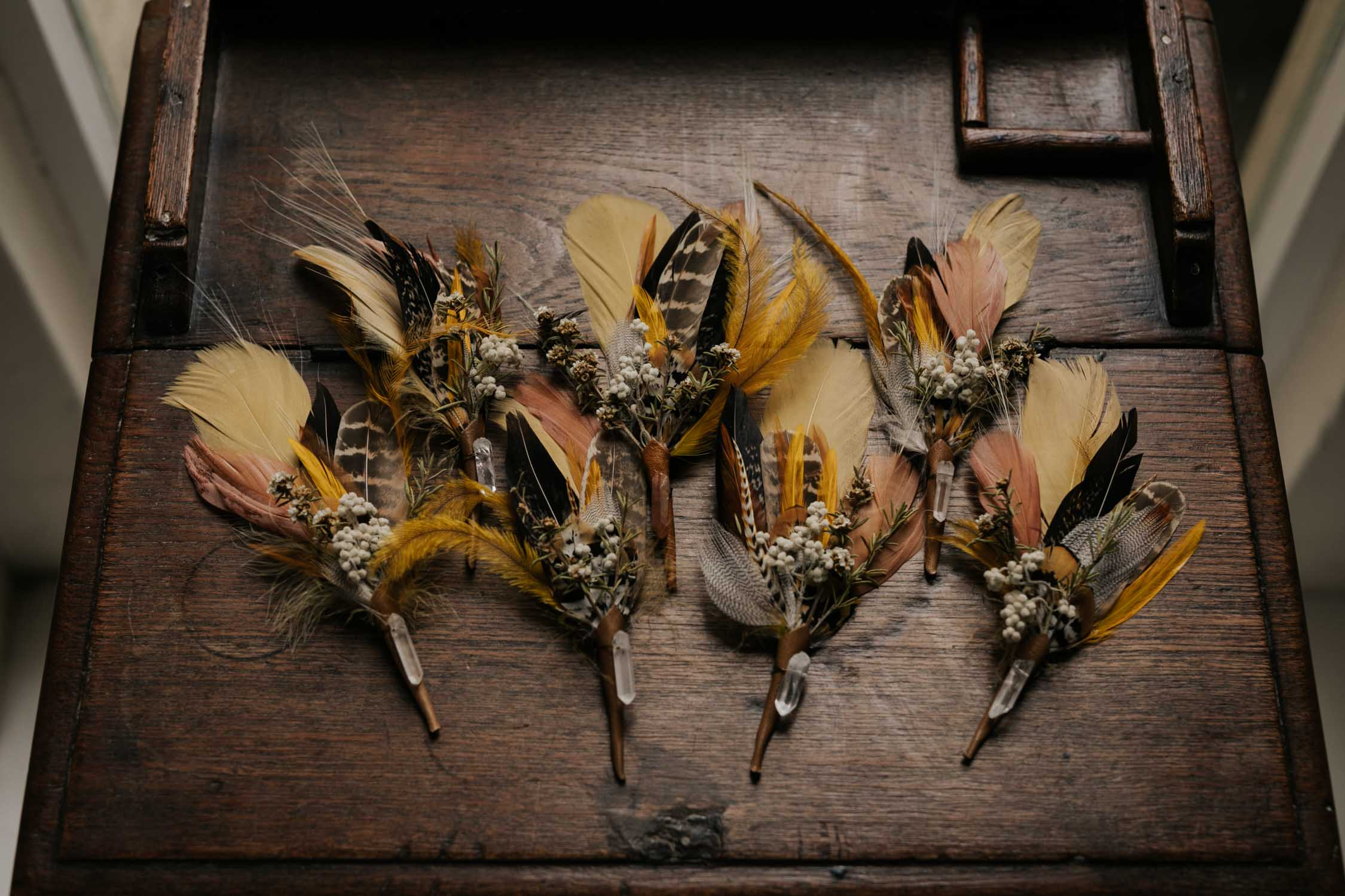 Groom and groomsmen foraged feather and dried flower boutineers for boho gypsy style wedding