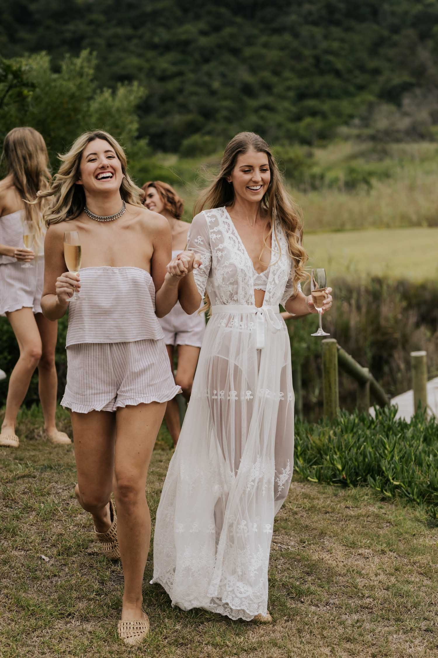 Beautiful Boho bride with long curly hair dressed in white lace PJs and gown dances and drinks champagne with her bridesmaids