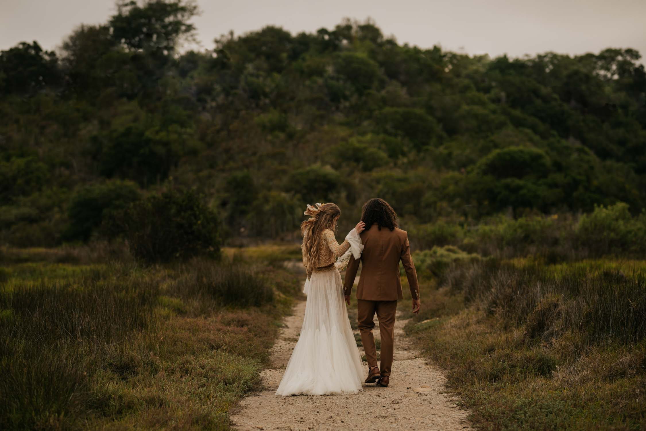 Boho bride and groom walk down dusty road at Emily Moon wedding venue in Garden Route